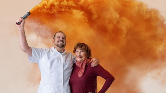 Blije verpleegkundige met baard maakt een oranje wolk en staat naast vrouw
