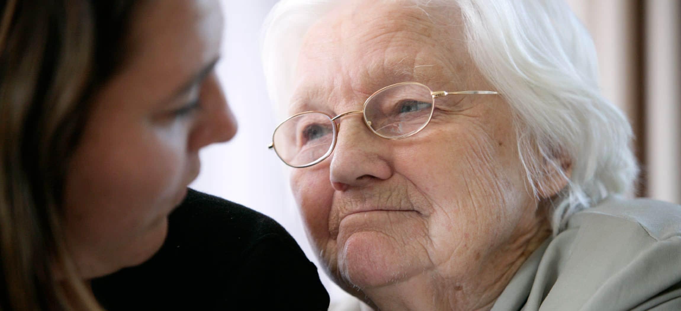 Close-up oude vrouw grijs haar kijkt met vertrouwen naar dochter