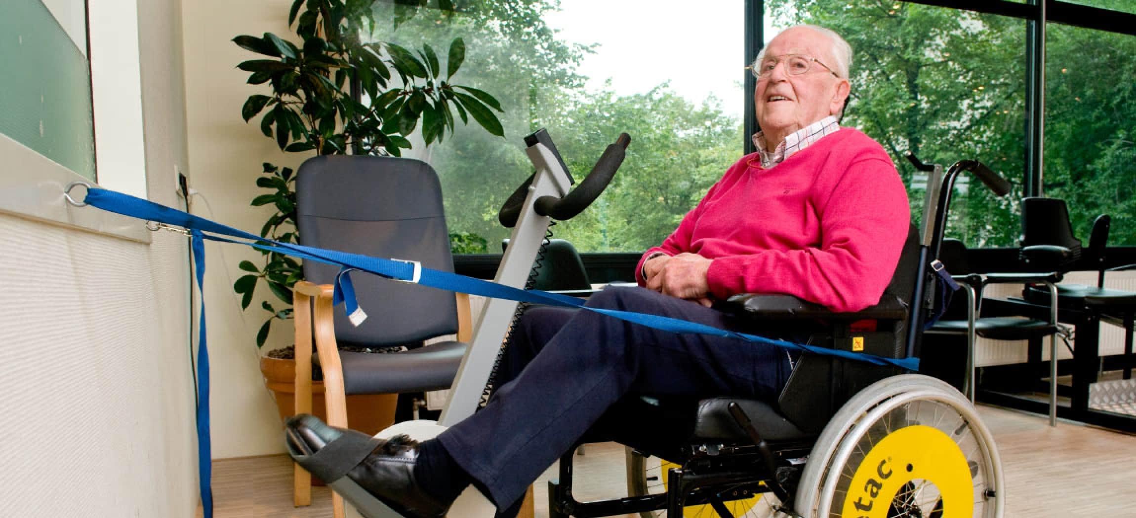 Blauwe trekband houdt rolstoel vast zodat man de fietstrainer kan gebruiken