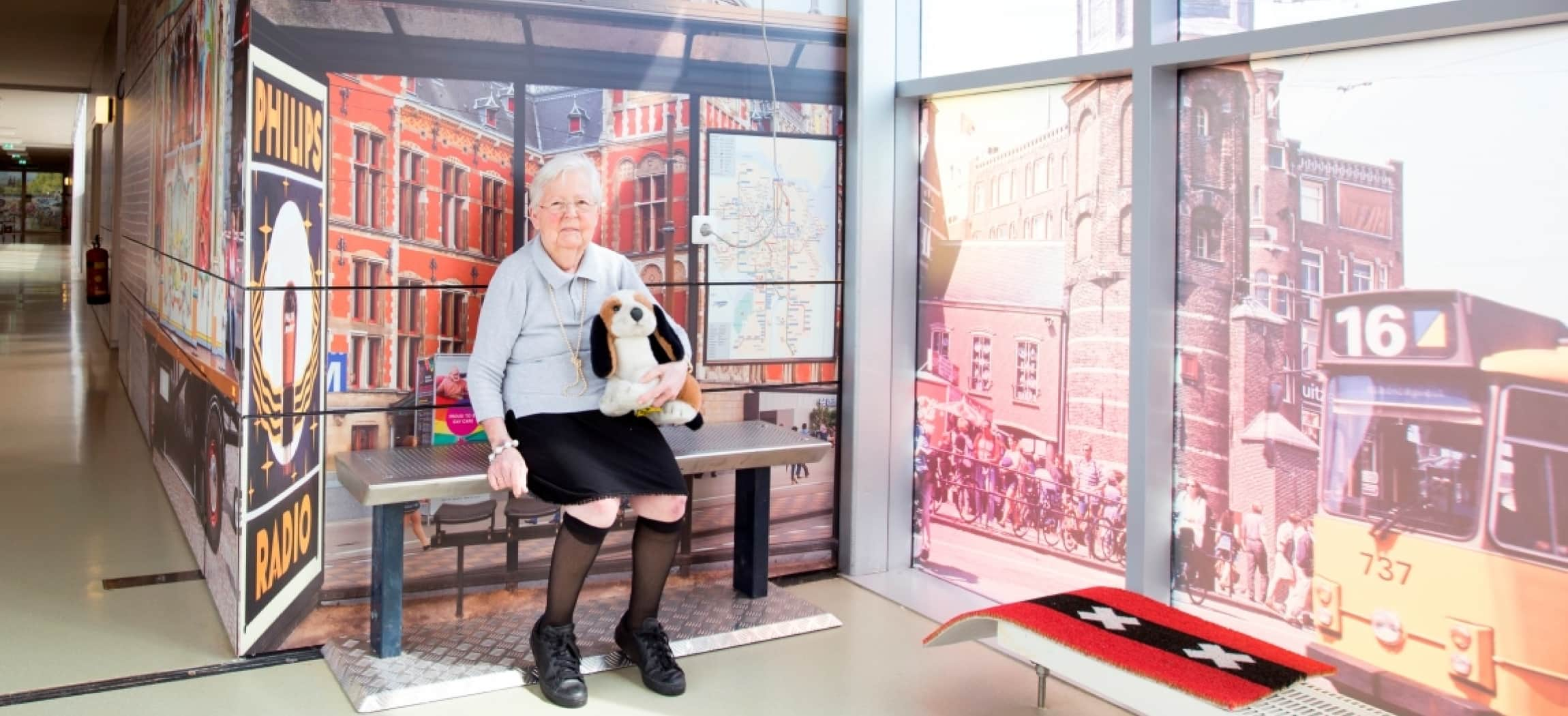 Oude dame zit op bankje in reminiscentie belevingsgang dementie verpleeghuis