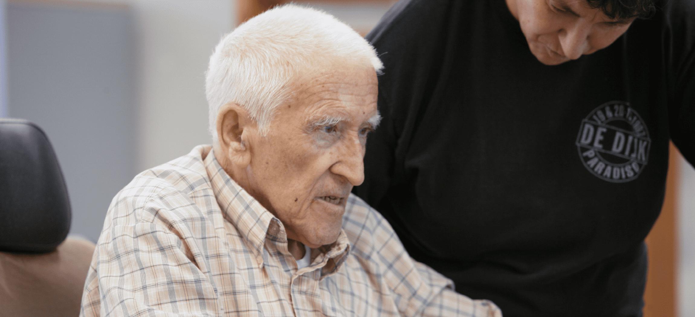 Oude man die zich inspant tijdens oefening bij een fysiotherapeut