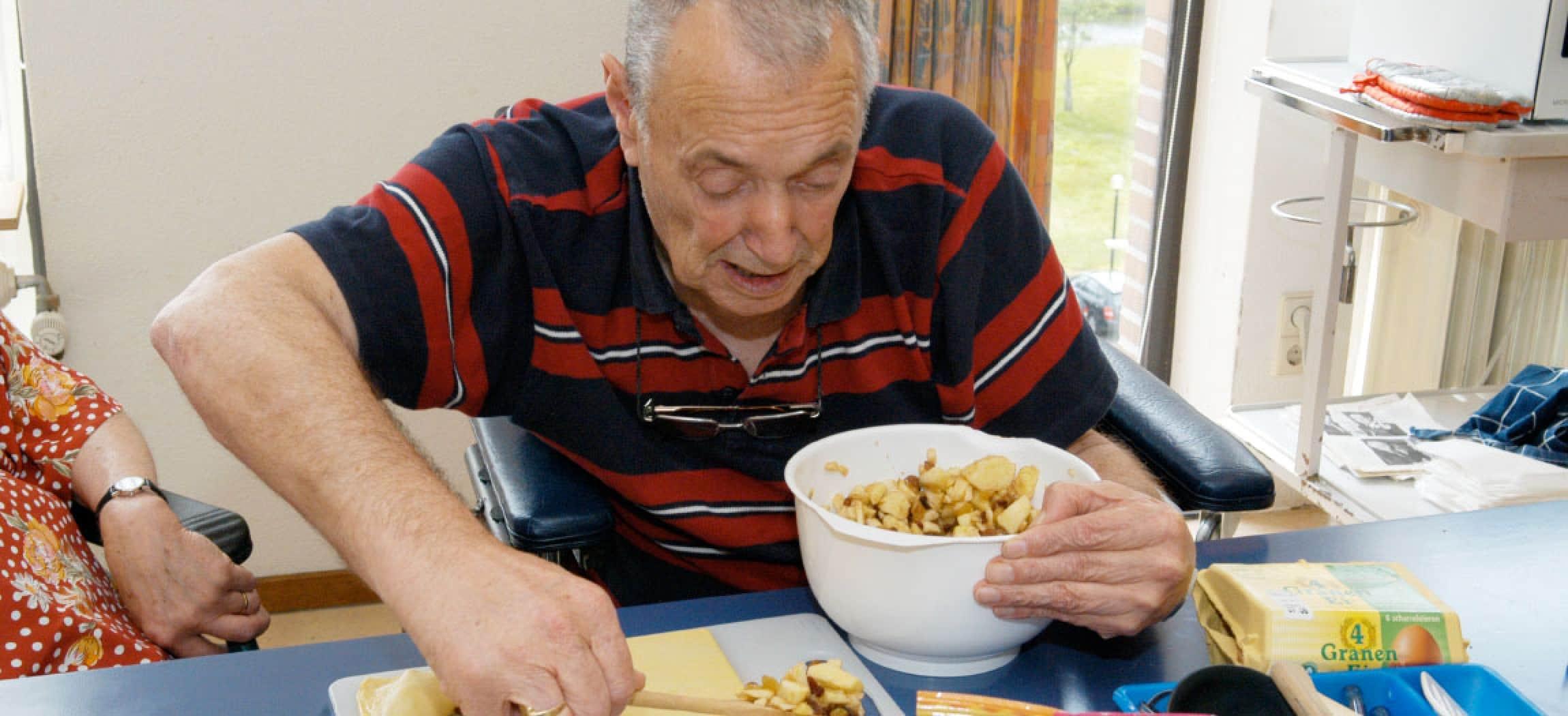 Opa maakt appelflappen aan tafel met kom appelpartjes