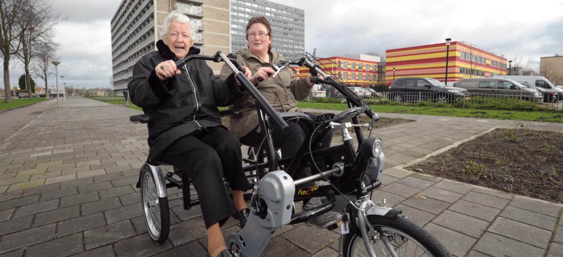 Twee dames oma buiten op duofiets met gebouwen op achtergrond