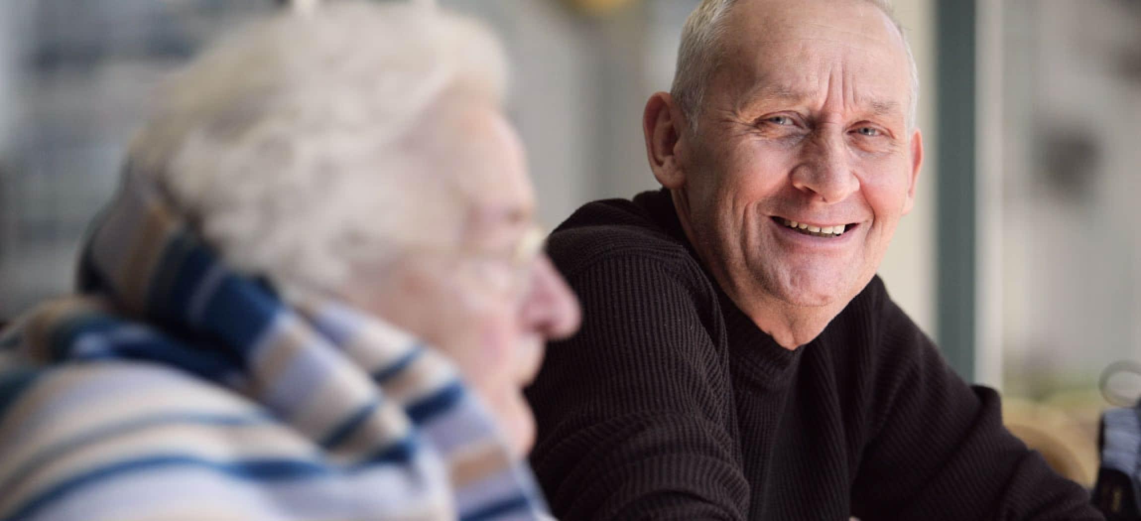 Aardige oude man zit en kijkt naar bejaarde vrouw close