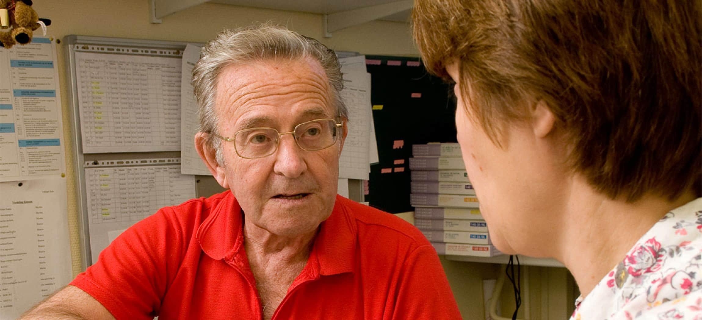 Man rood shirt bril kijkt en luistert naar logopedist met werkschema