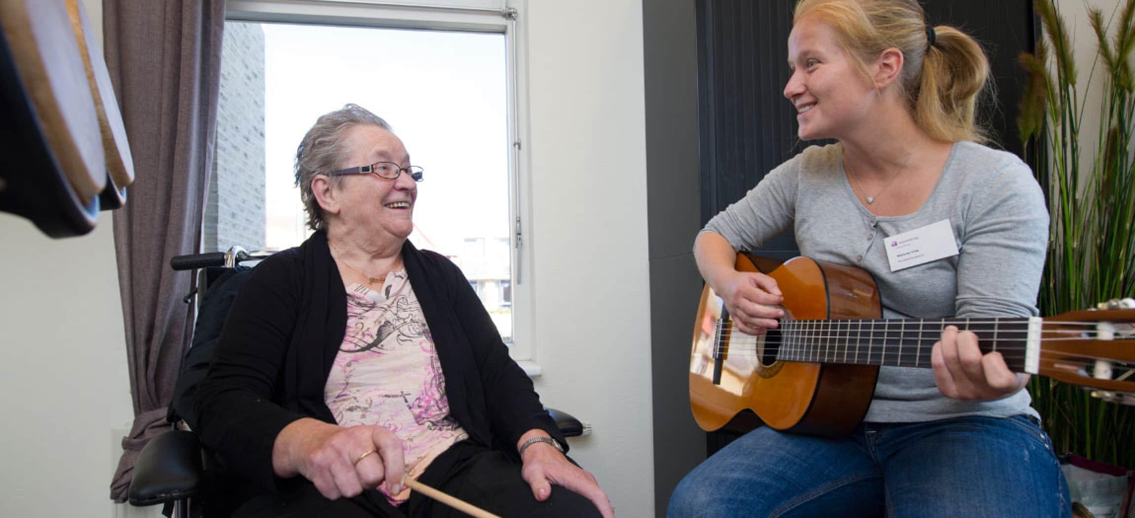 Jonge muziektherapeut met gitaar blond haar zingt voor oudere dame in rolstoel