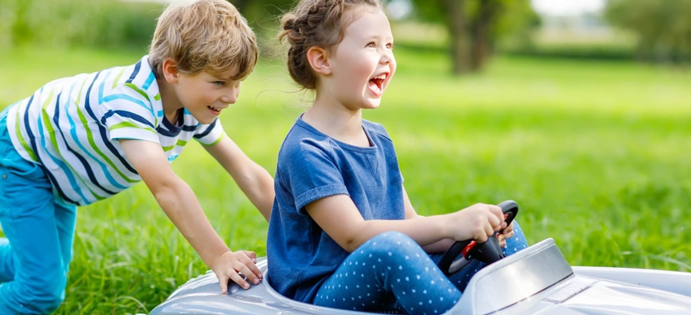 Meisje zit in speelgoedauto buiten in tuin en wordt geduwd door jongen