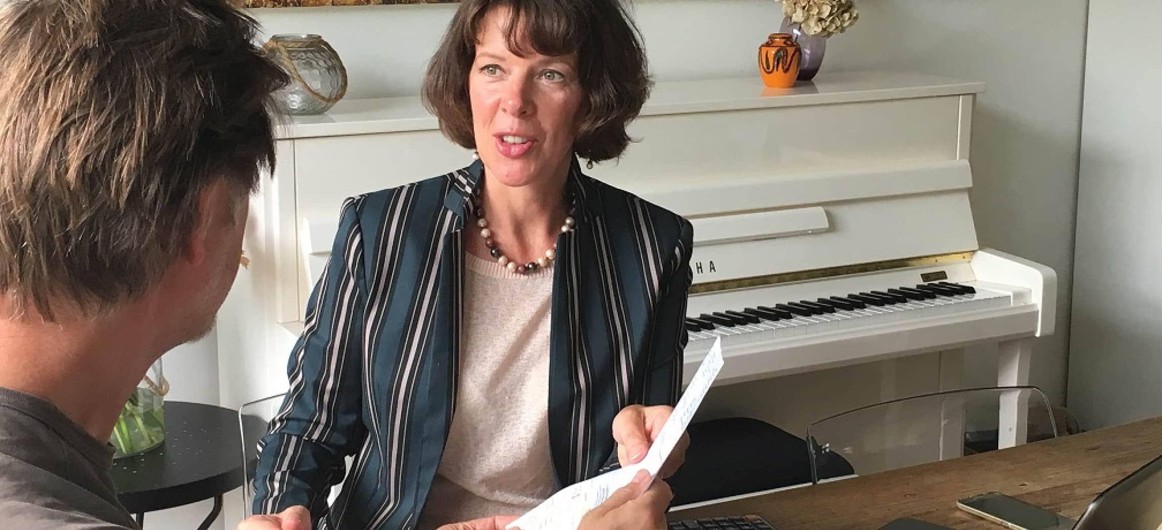 Man overhandigt vrouw een papier met witte piano op achtergrond