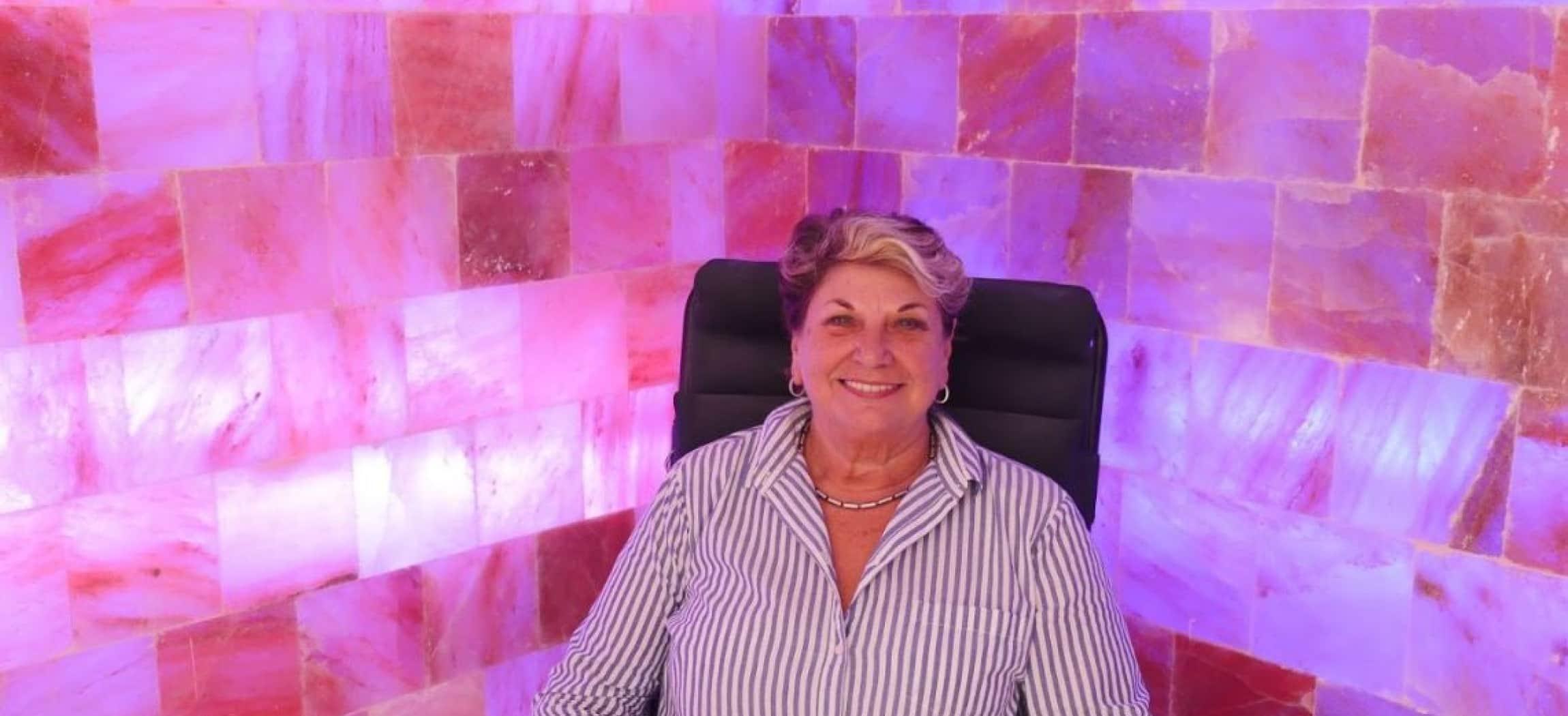Muur van roze zouttegels met een vrouw zittend in een stoel