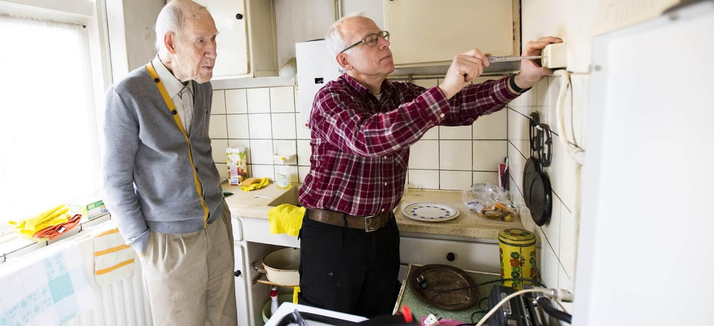 Zeer oude man kijkt hoe andere man een stopcontact repareert met schroevendraaier in oude keuken