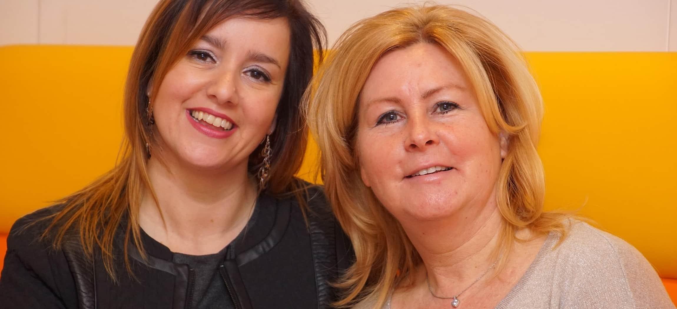 Portret van twee vrouwen bruin haar en blond haar tegen gele muur achtergrond