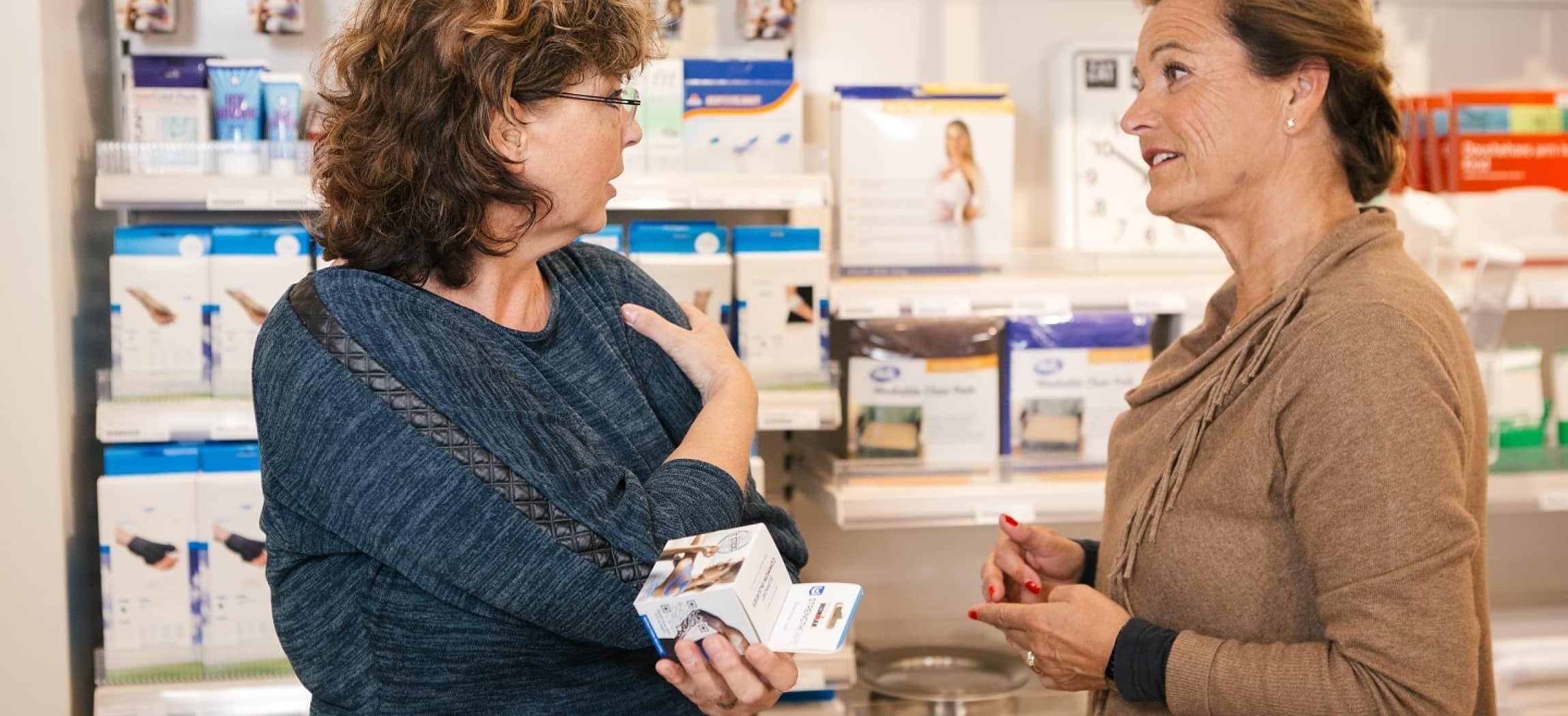 Twee vrouwen praten met elkaar in winkel met verbandmiddelen