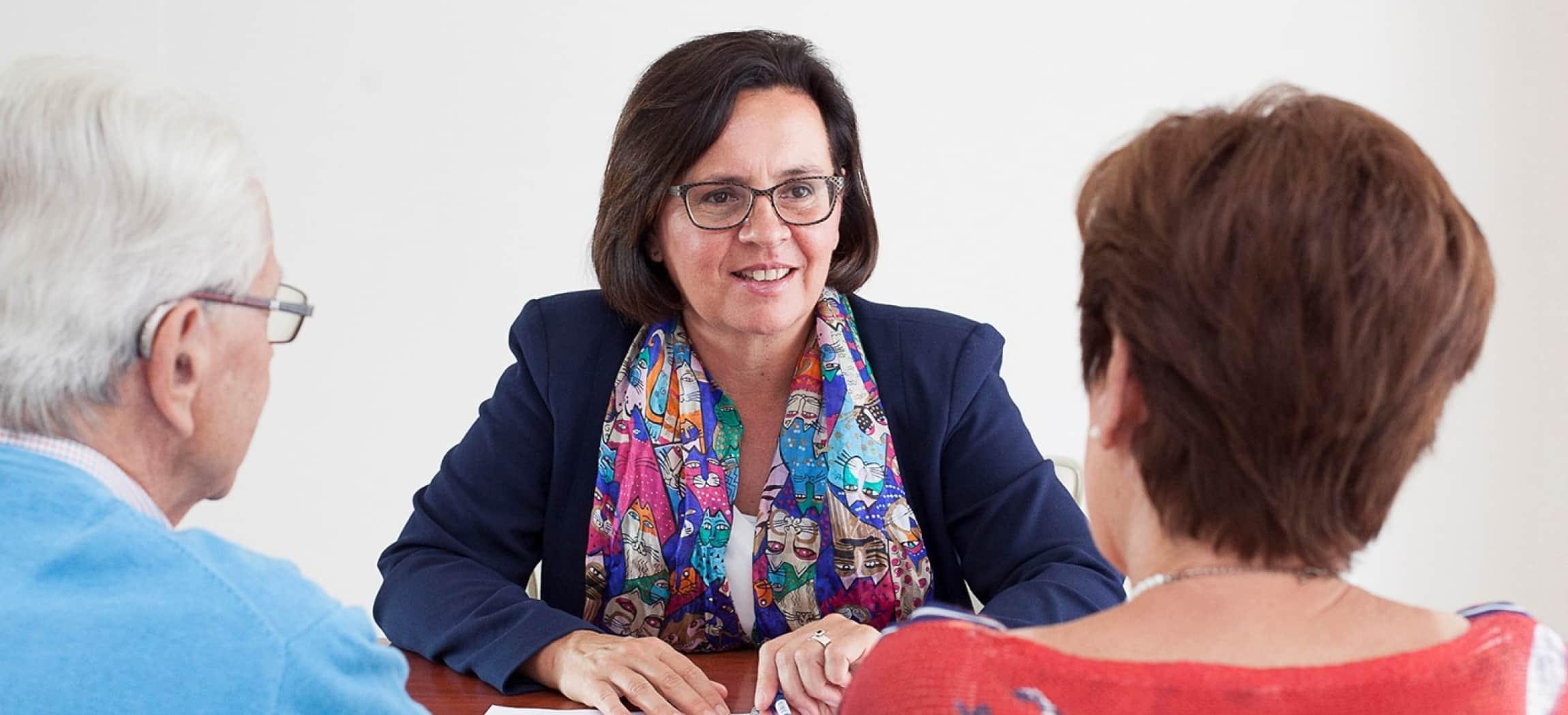 Vrouw met bril en colbertjasje geeft advies advies aan man en vrouw