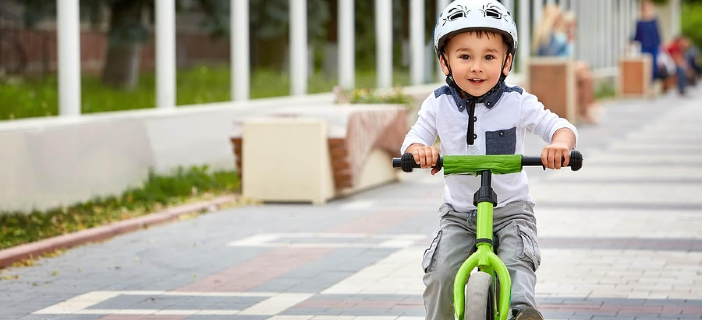 Peuter op groen fietsje met witte helm