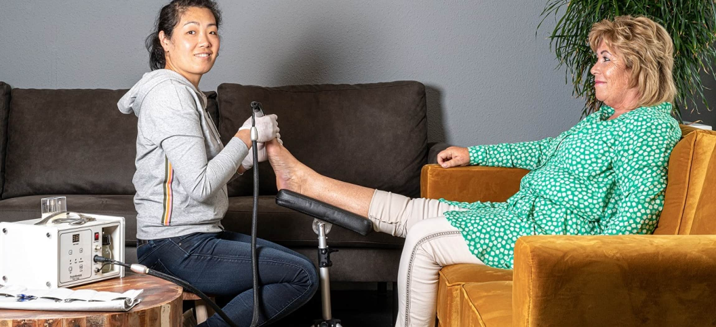 Vrouw met professioneel medisch pedicure toestel behandelt voet van vrouw zittend in fauteuil thuis