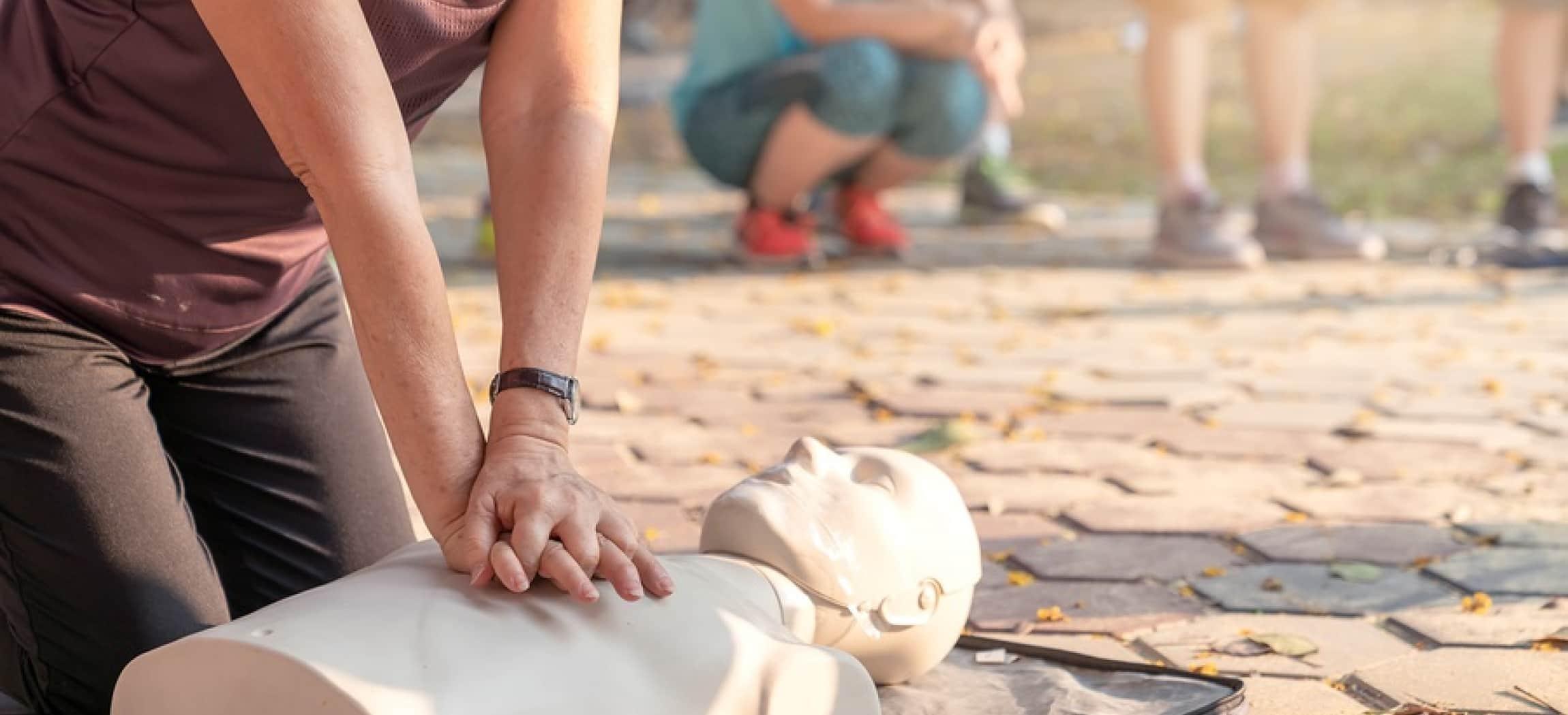 Vrouw knielt op grond en geeft hartmassage aan oefenpop EHBO