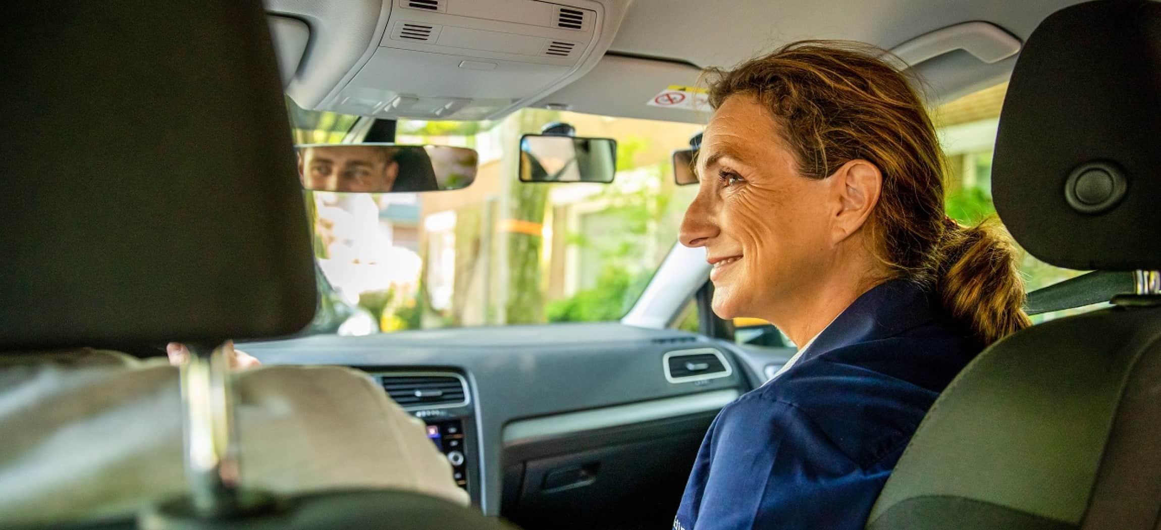 Vrouwelijke rij-instructeur zit op passagiersstoel en kijkt naar leerling achter het stuur