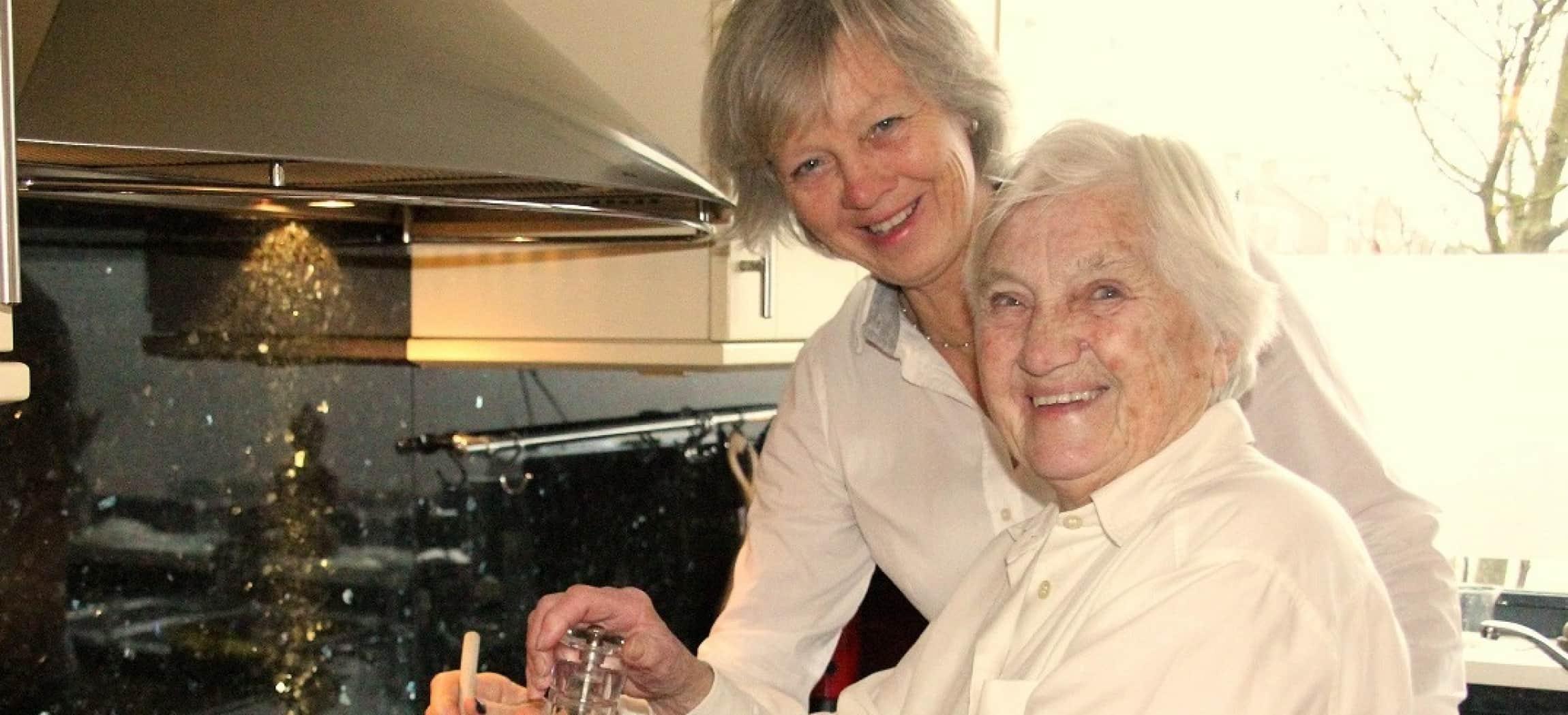 Twee oudere vrouwen in keuken met witte blouses