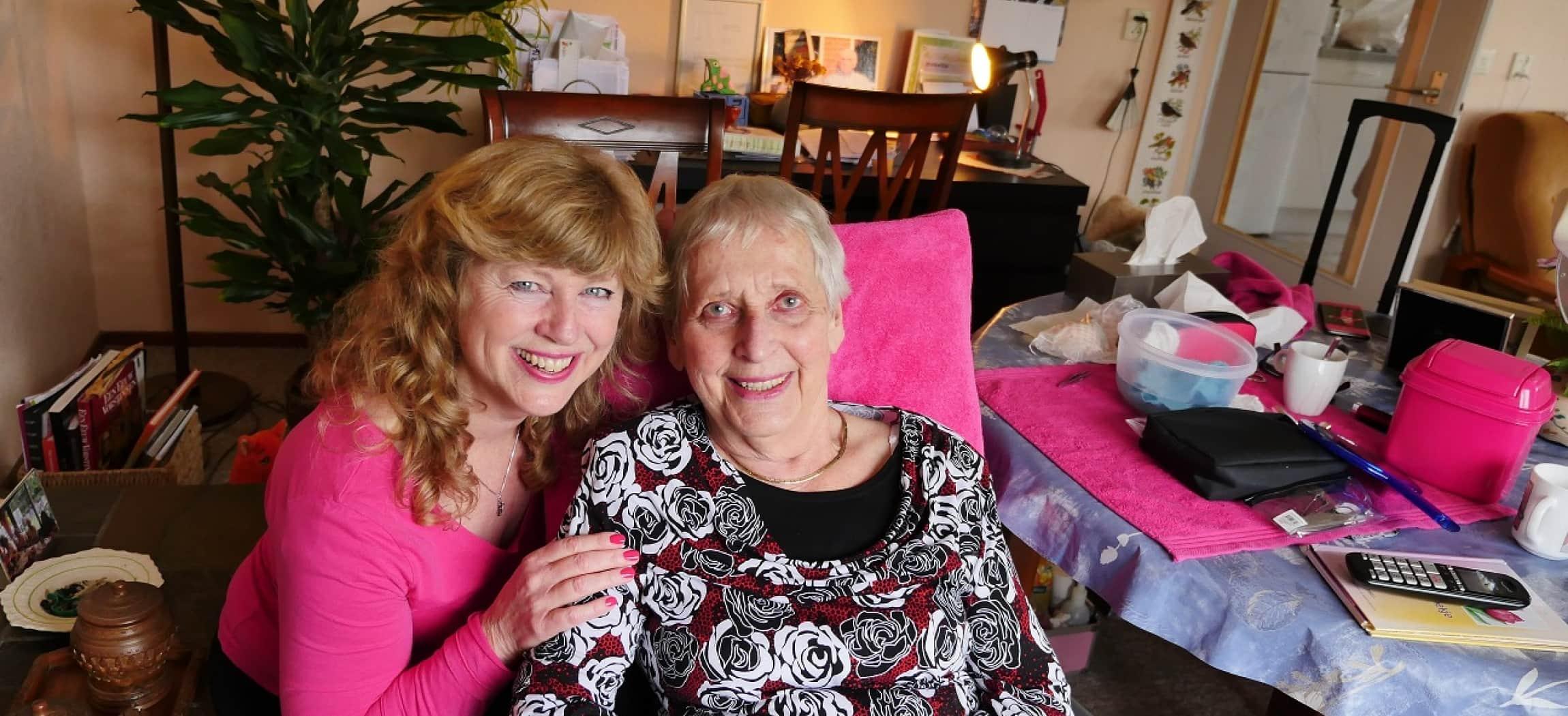 In gezellige woonkamer twee vrouwen met roze spullen schoonheidsbehandeling op tafel