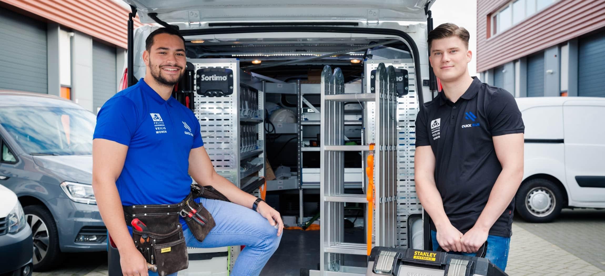 Twee jonge mannen in blauwe t-shirts naast bus van slotenmaker Quick Blue
