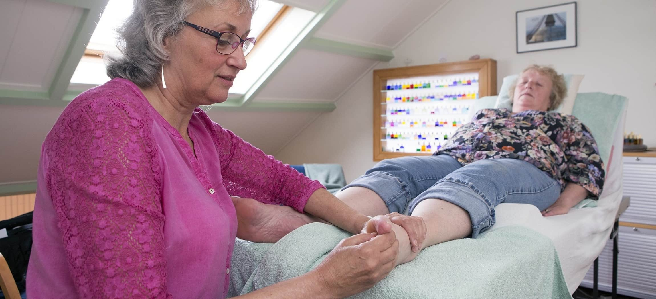 Vrouw met roze blouse masseert de voet van een vrouw die op een massagetafel ligt