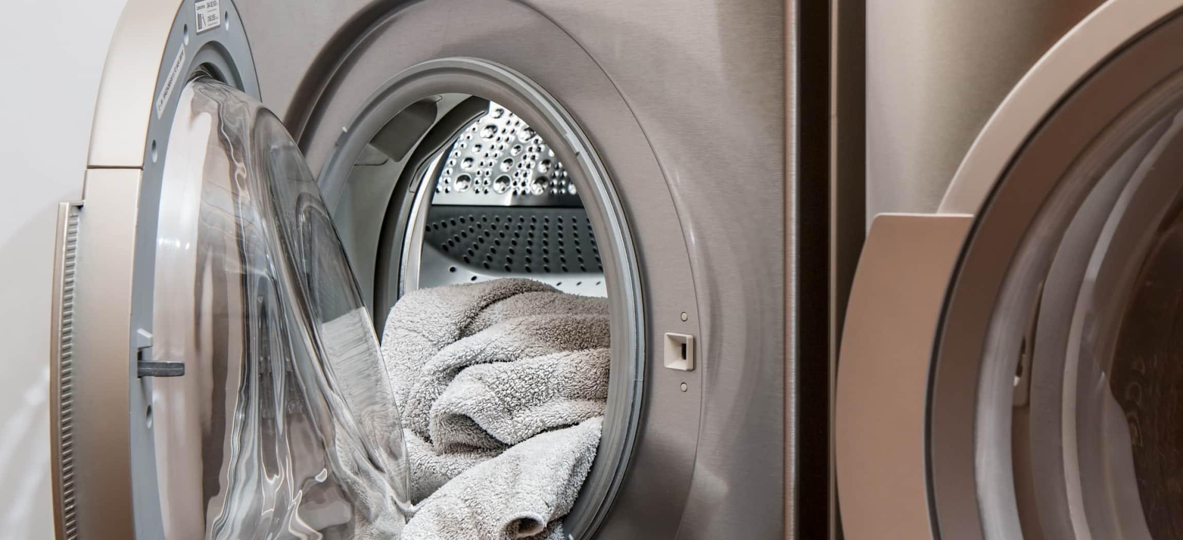 Wasmachine met deur half open, het witte wasgoed hangt eruit