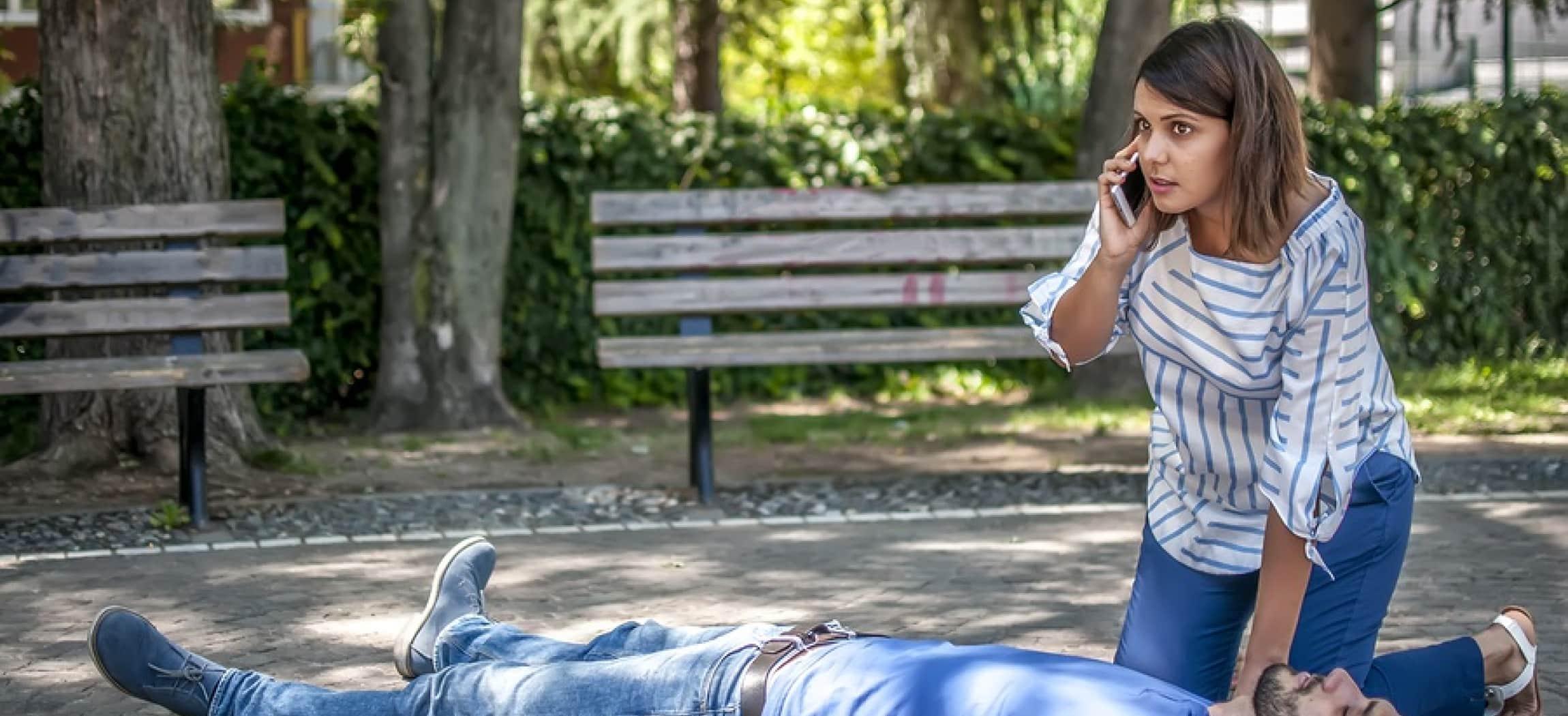 Vrouw knielt bij man die op de grond ligt in een park en ze belt met haar mobiele telefoon