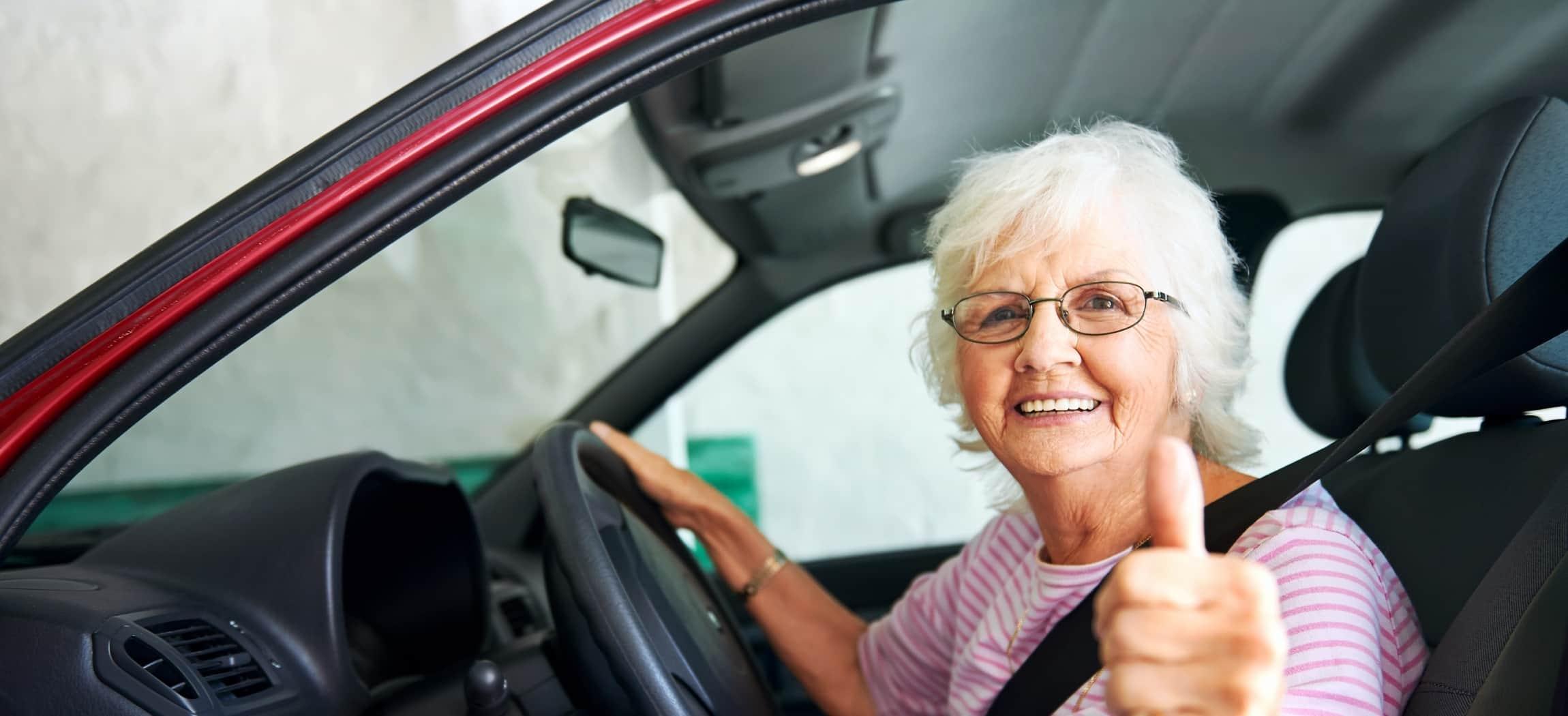 Vrouw grijs haar met bril zit achter het stuur in een auto met duim omhoog