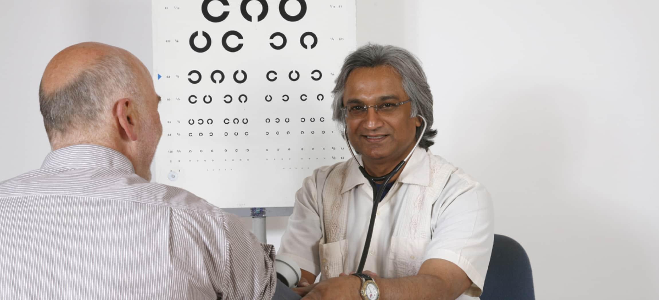 Arts doet een bloeddrukmeter om bij arm van man met poster oogtest