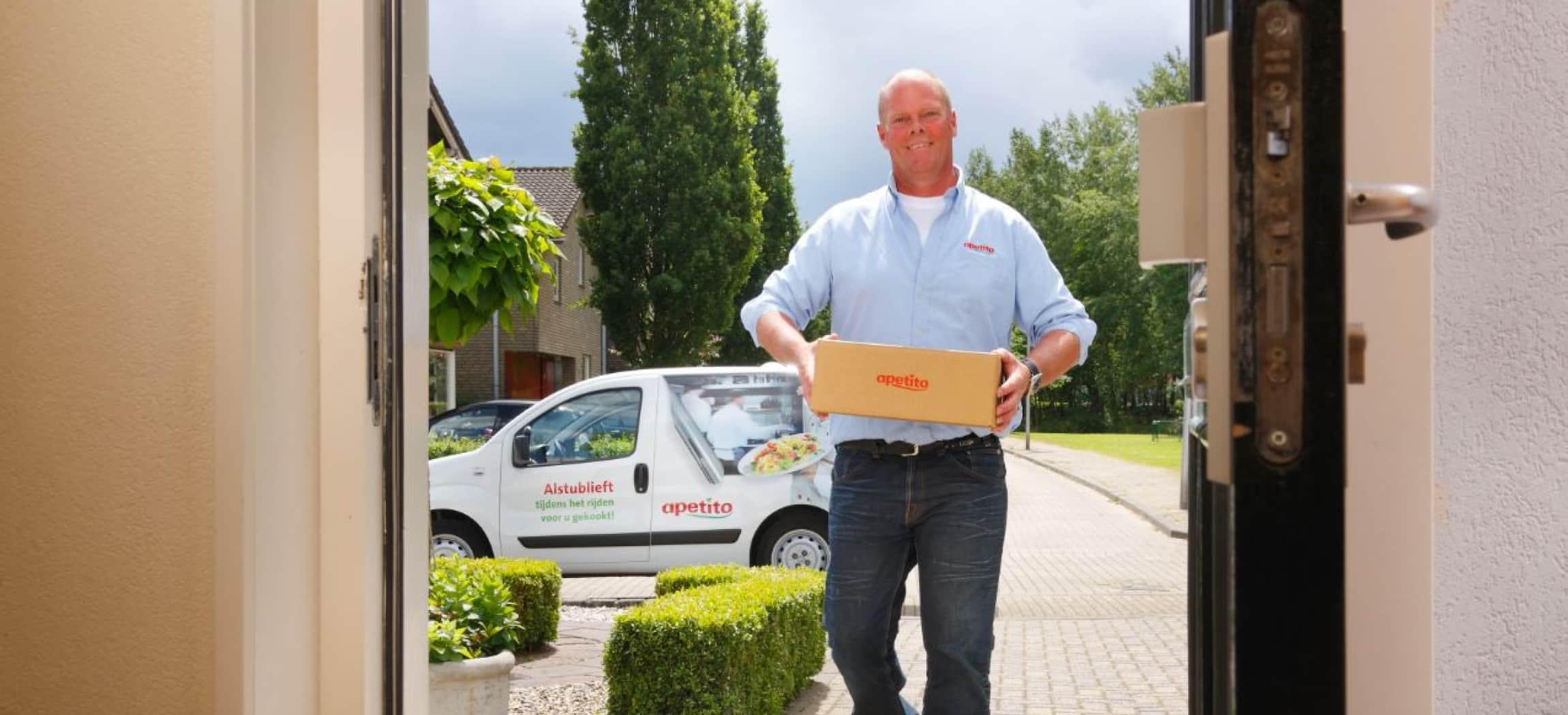 Mannelijke thuisbezorger met doos Apetito aan voordeur met witte bezorgauto