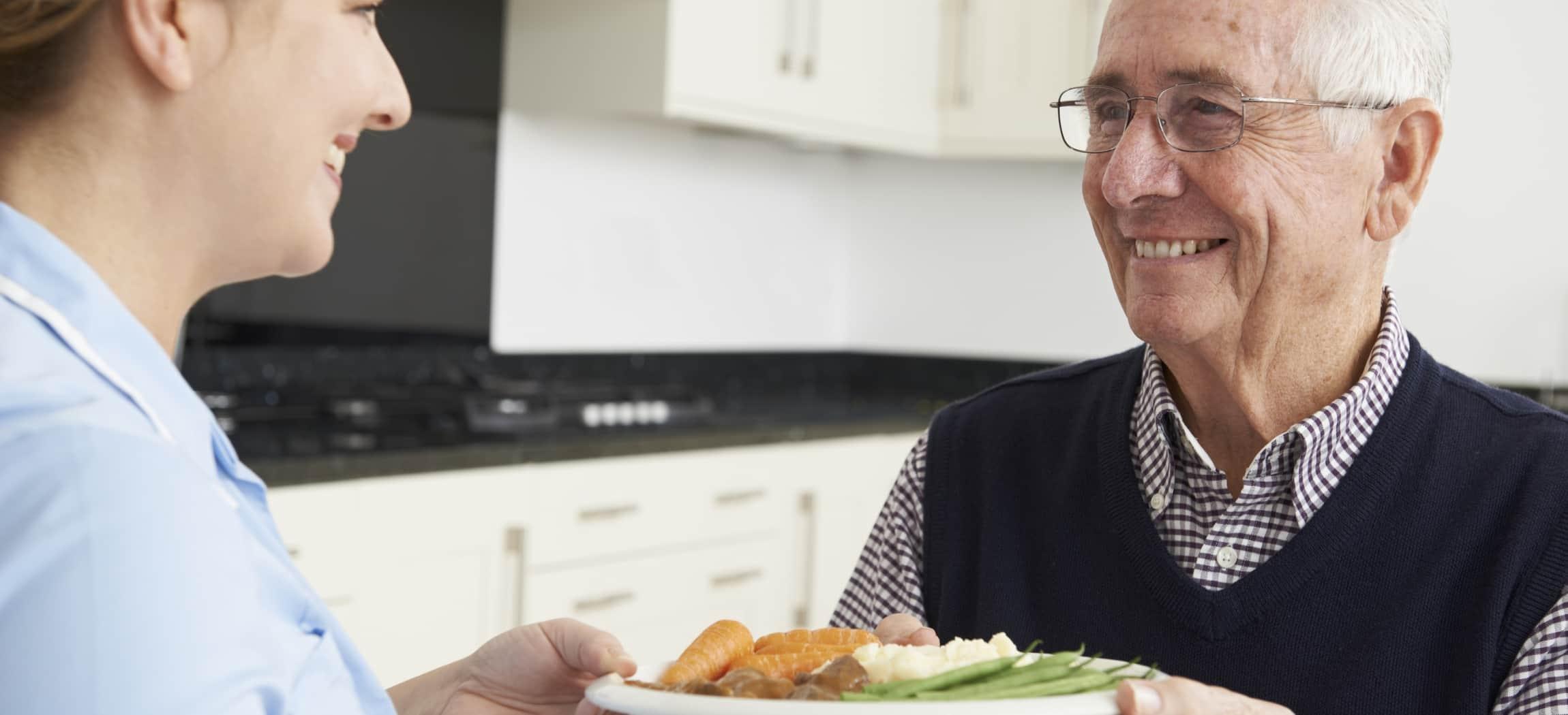 Vrouw overhandigt een bordje eten wortelen sperziebonen aan man met overhemd en spencer
