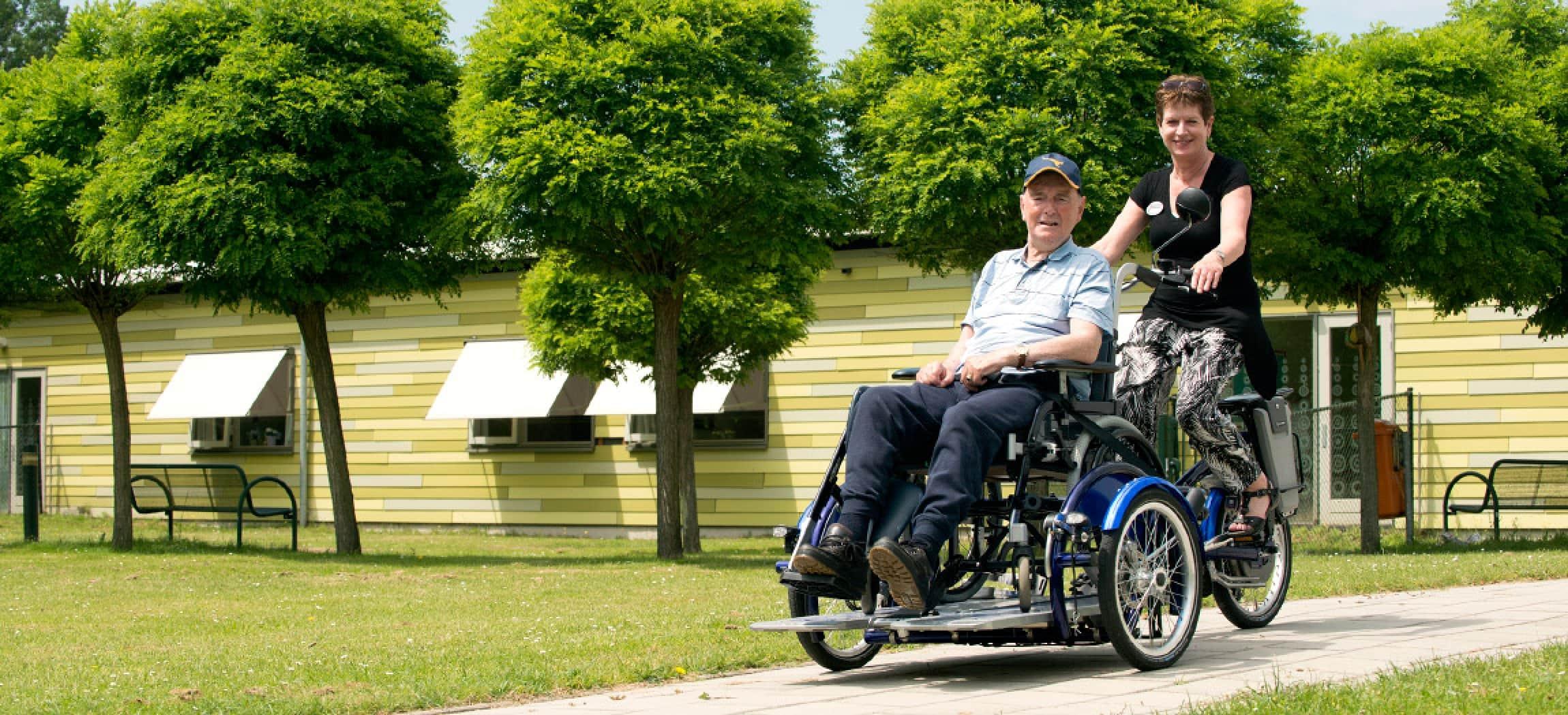 Rolstoelfiets met oudere man in rolstoel en verzorgende - rolstoeltransportfiets