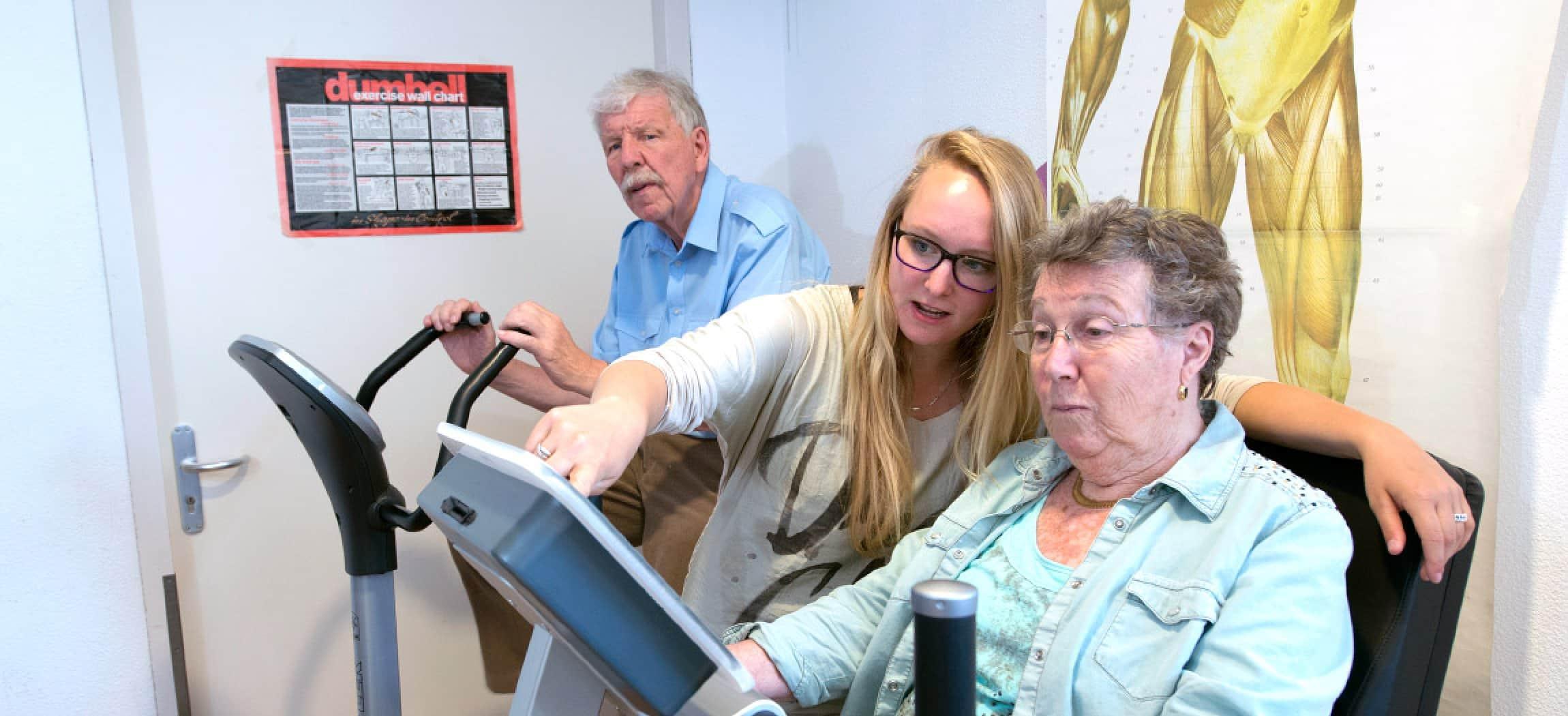Ergotherapeut helft oudere vrouw met fitness fiets