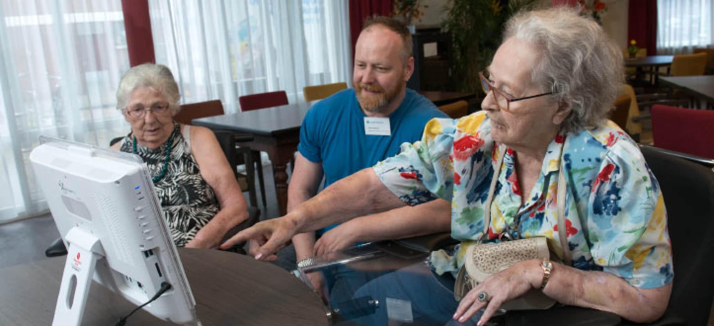 Bejaarde vrouw wijst naar computerscherm
