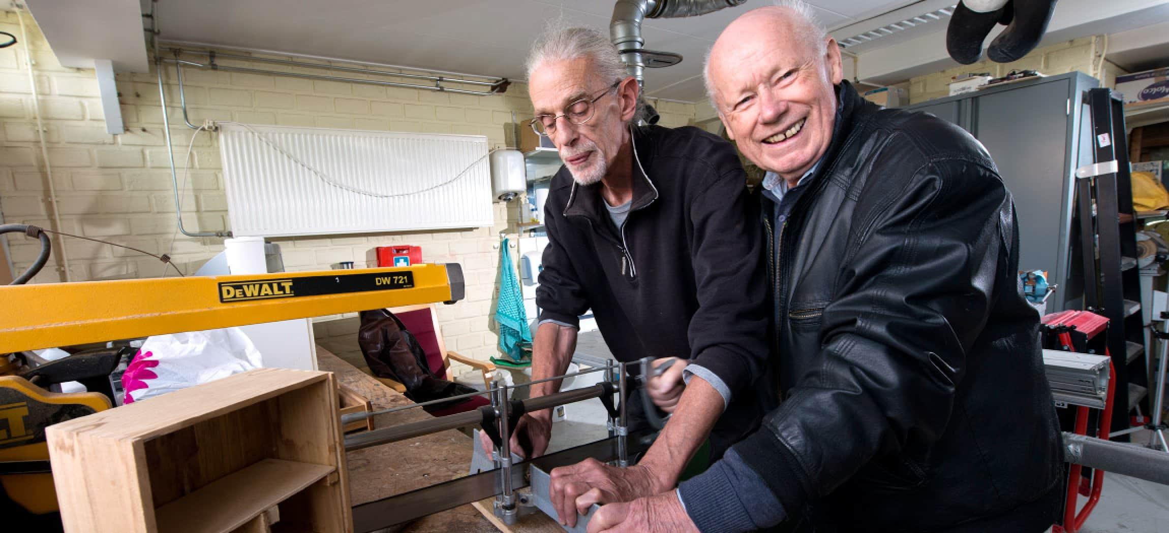Twee oudere mannen in doe-het-zelf timmer werkplaats