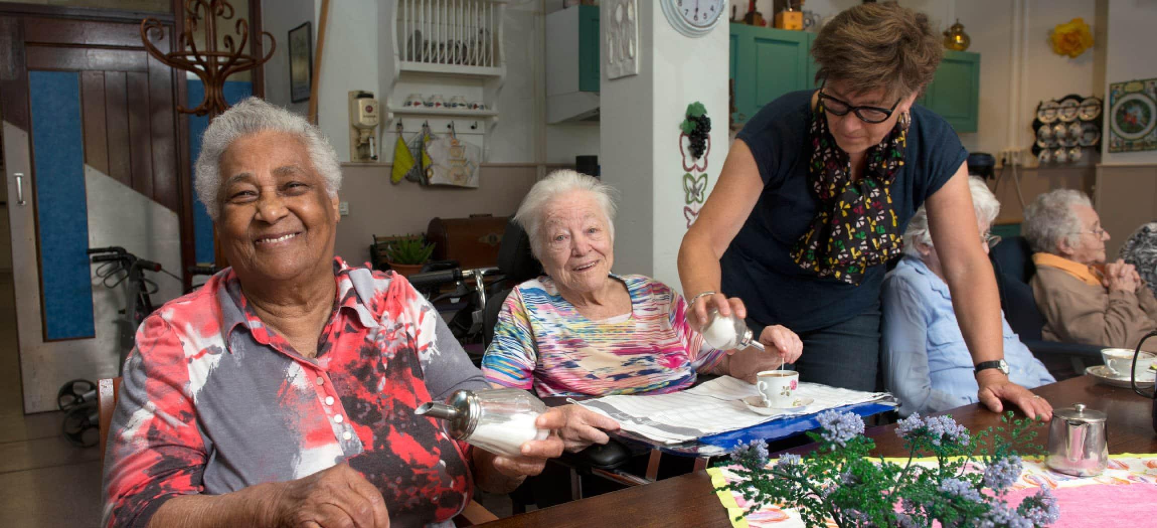 Lieve oude vrouwen aan gezellige tafel met koffie en knutselwerk