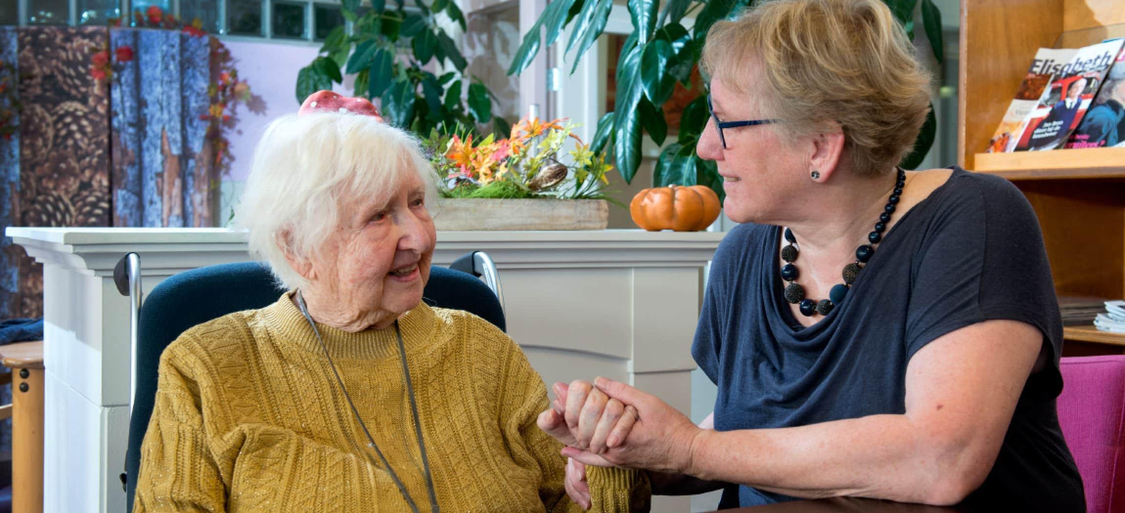 Vrouw houdt de hand vast van een oude oma met grijs haar