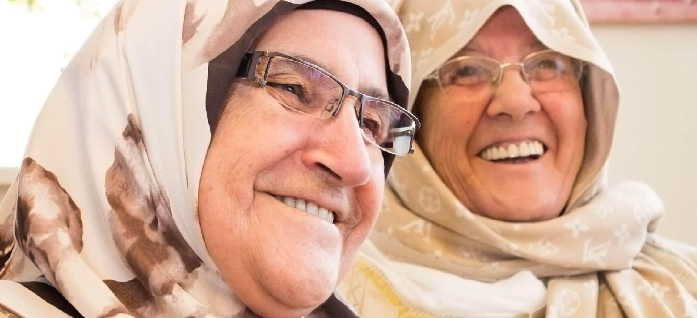 Twee vrolijke oudere dames met hoofddoek, omslagdoek of hijab
