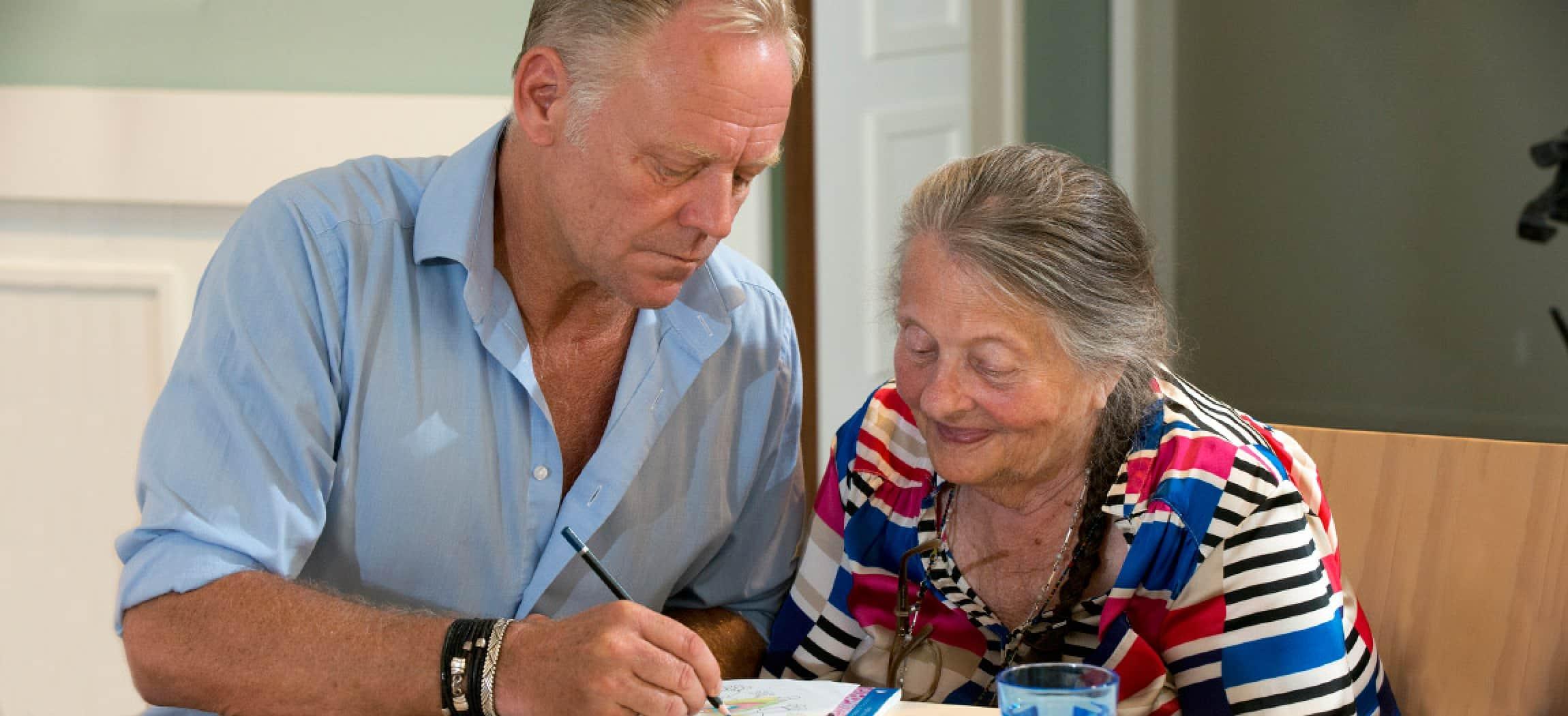 Man maakt tekening voor een oudere en blij kijkende vrouw