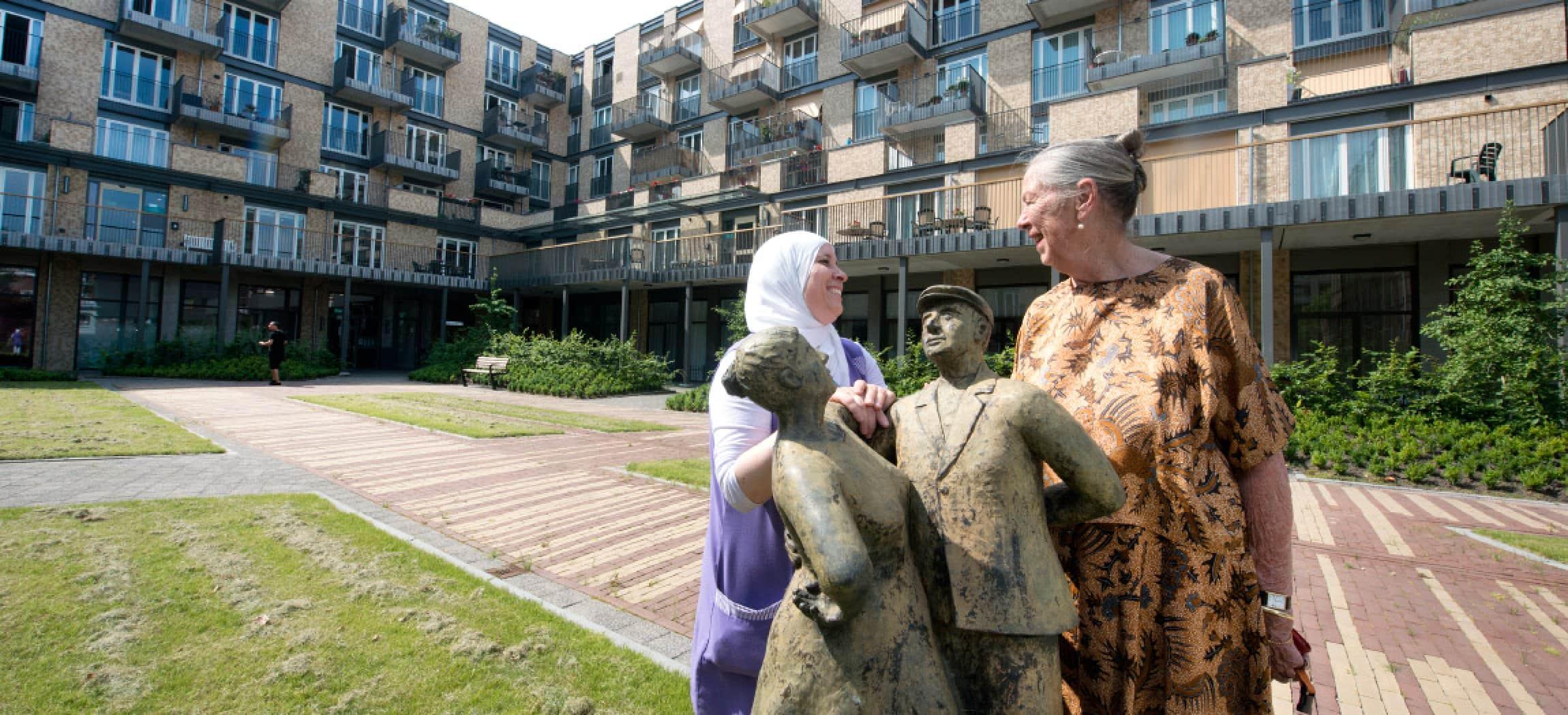 Stadse binnentuin met standbeeld en 2 vrouwend