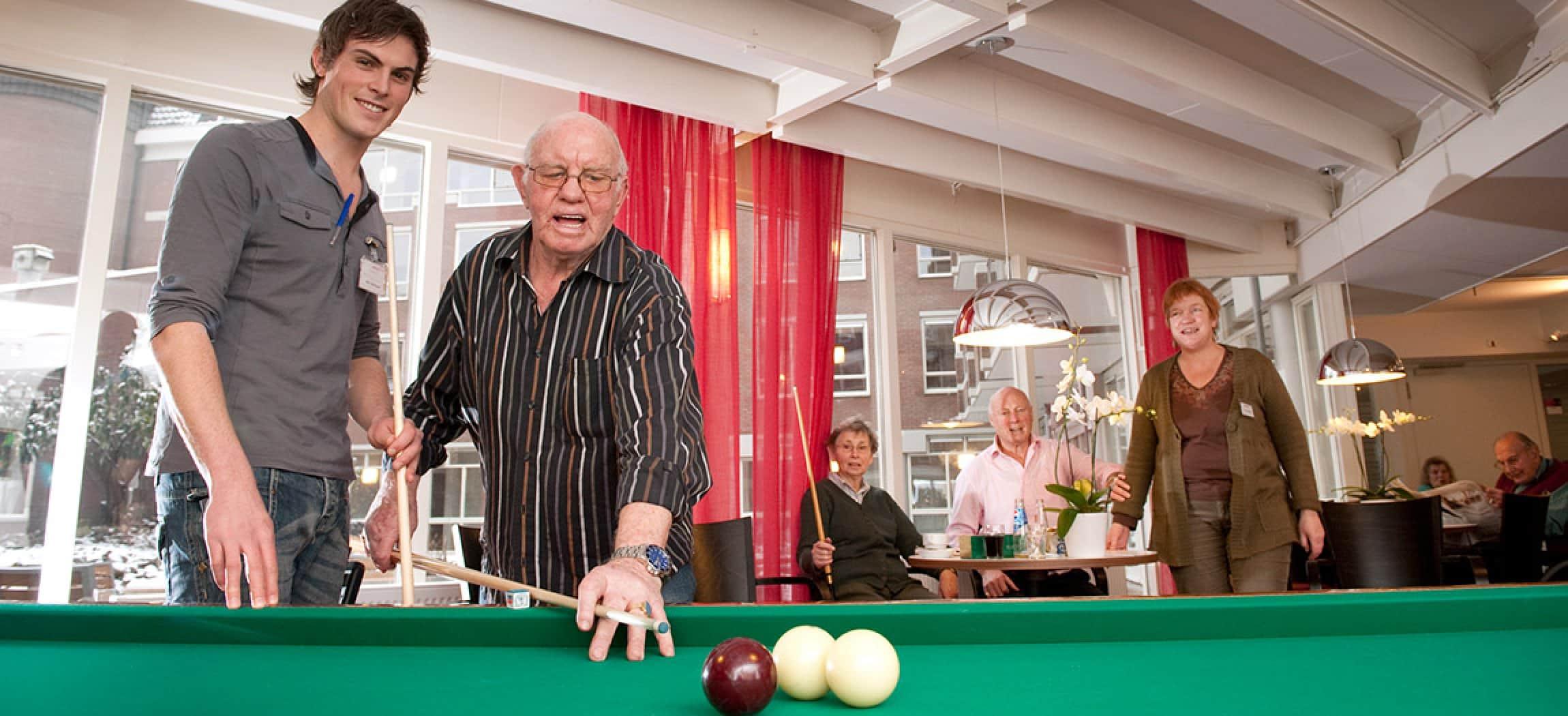Oude man speelt biljart met keu en mannelijke verzorgende kijkt mee