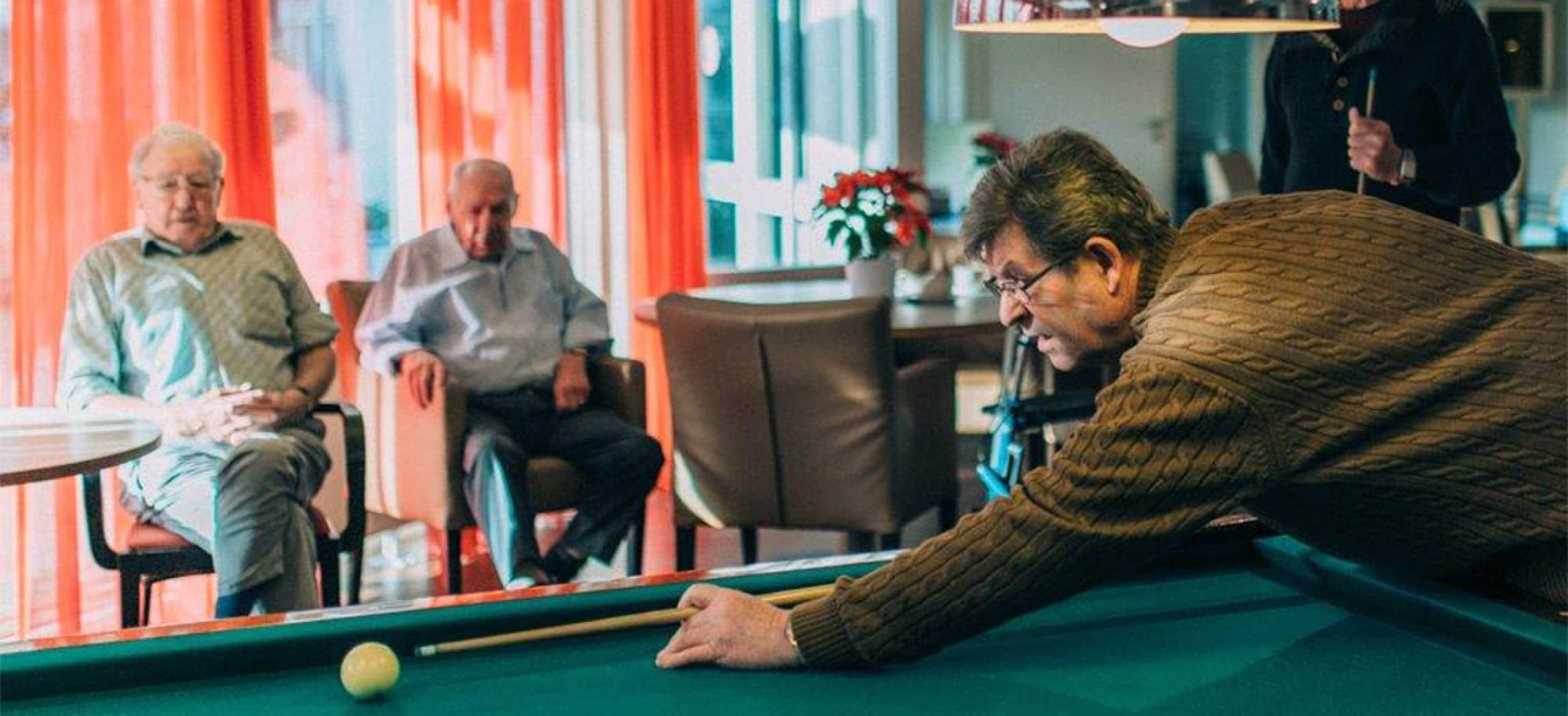 Biljarttafel en oudere mannen die naar biljartspel kijken