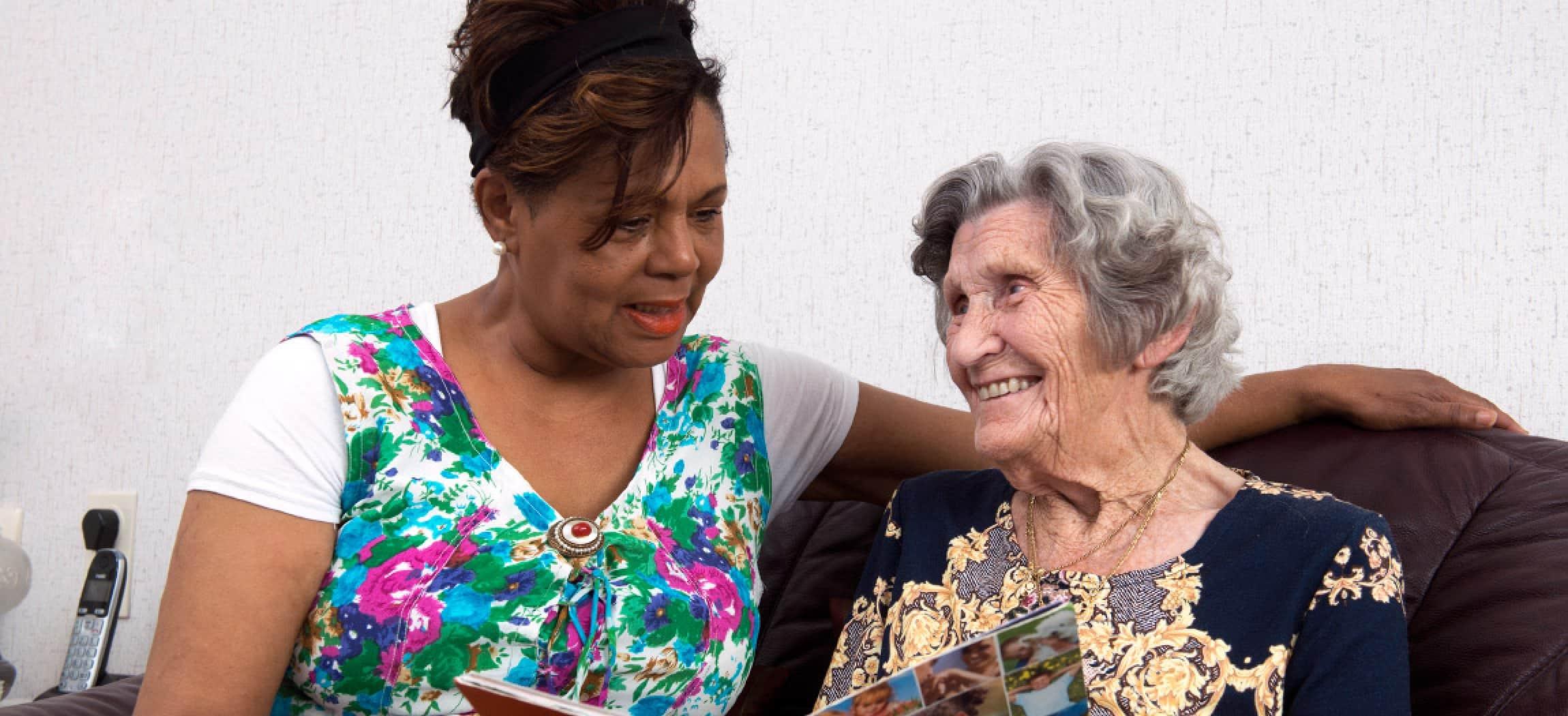 Woonbegeleider en oudere vrouw lezen samen een tijdschrift