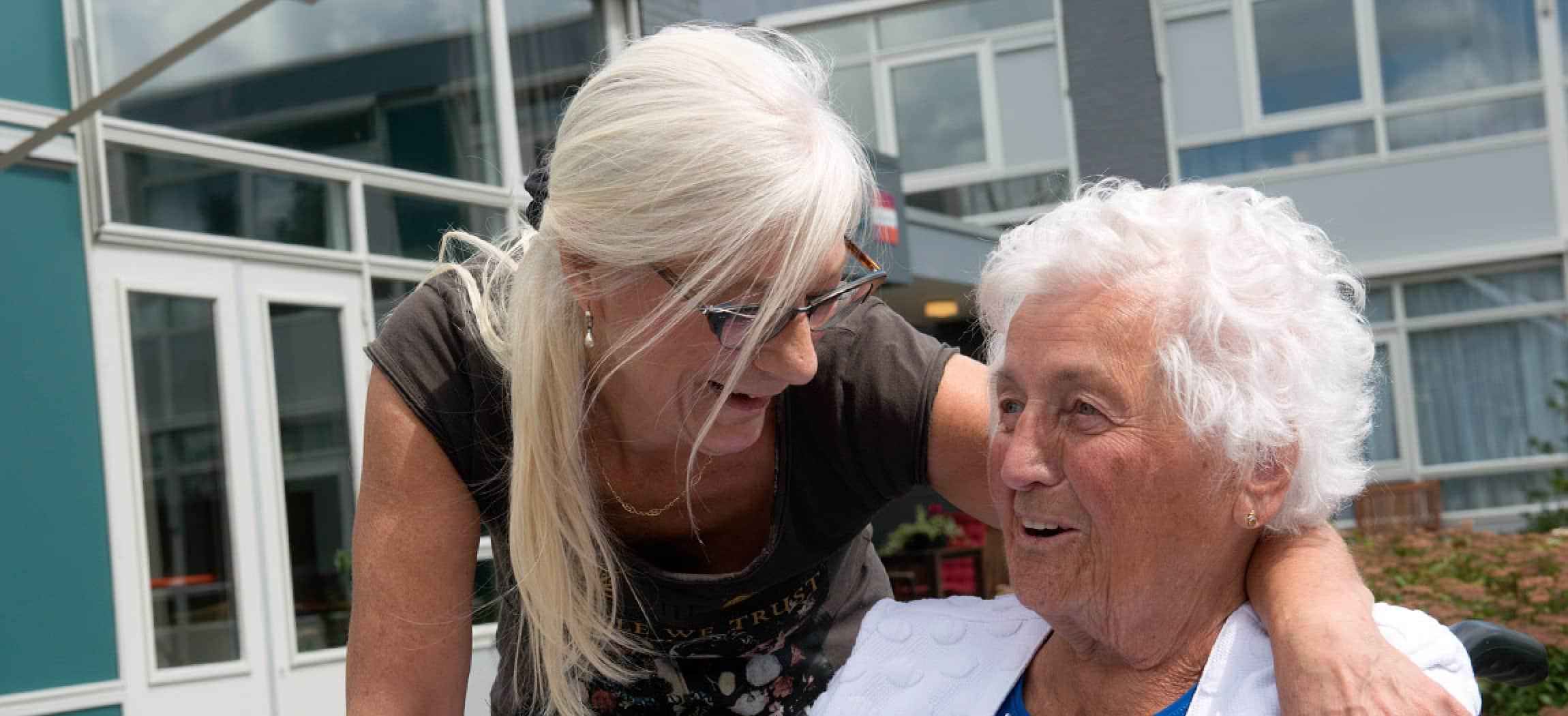 Vrouw met lang grijsblond haar omarmt bejaarde vrouw, gebouw op achtergrond