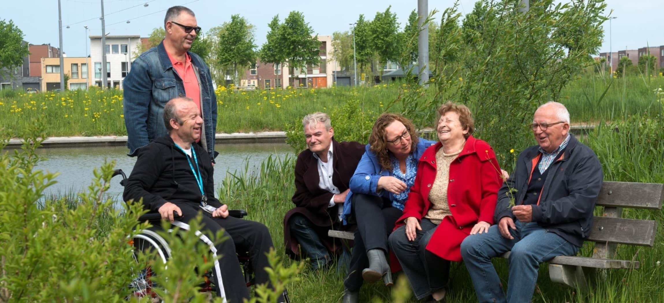 Ouderen zitten gezellig op een bankje in de groene natuur met meertje in Hoofddorp