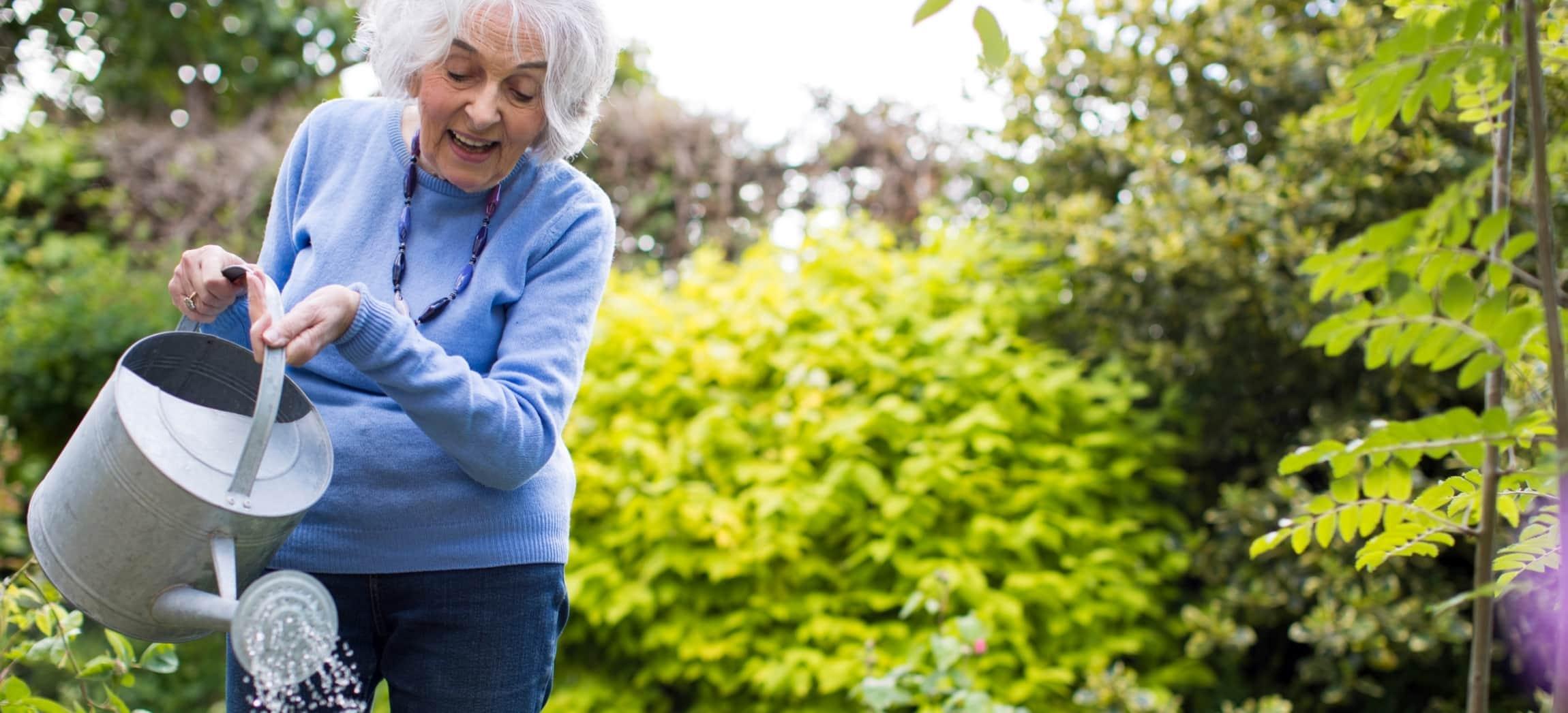 Vrouw geeft planten water met gieter in tuin met groene struiken