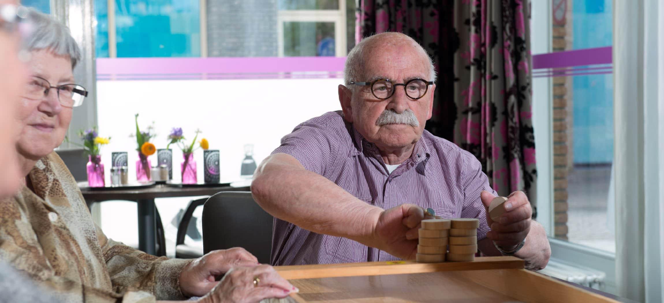 Sjoelen: oudere man met snor en bril speelt het Oud-Hollandse spel sjoelen