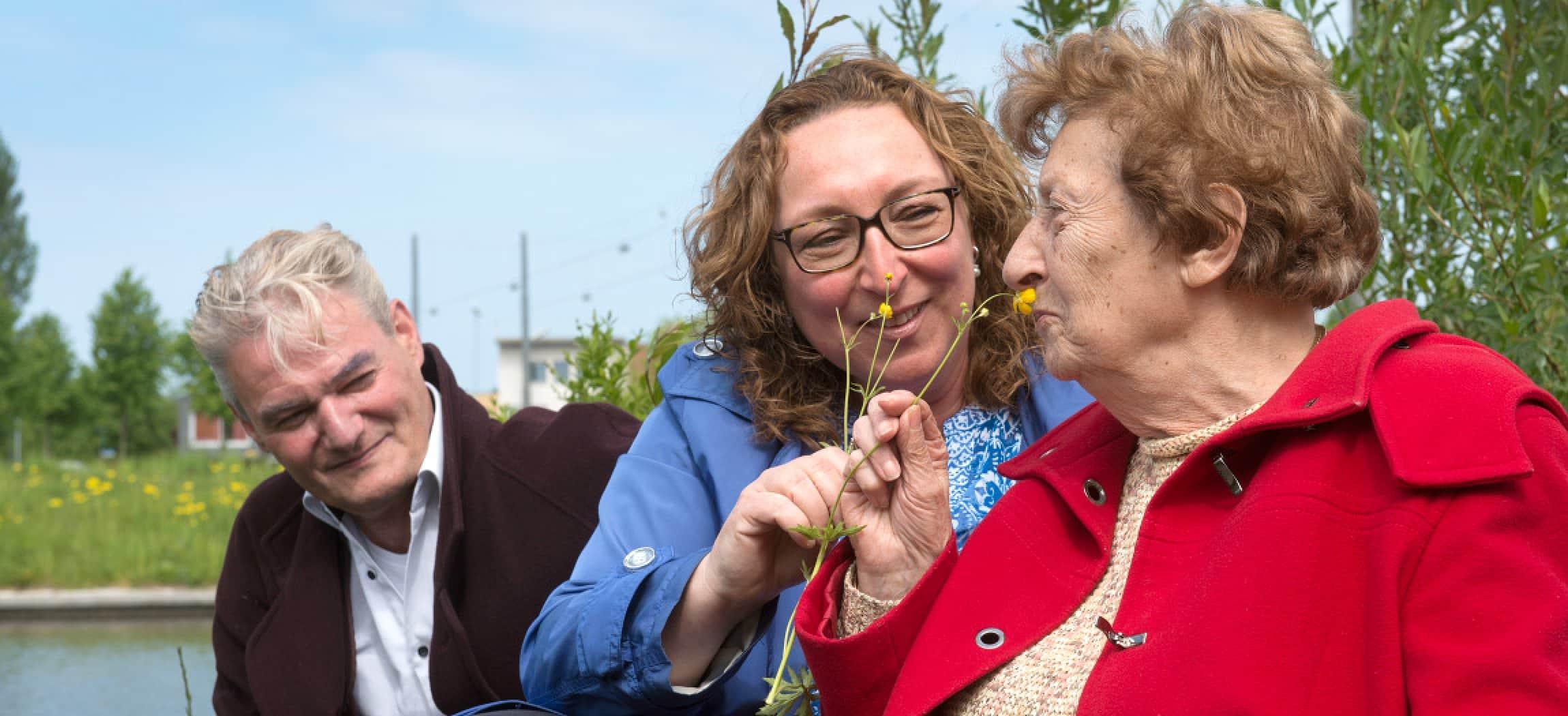Jonge en oudere vrouw ruiken aan een bloem in de natuur