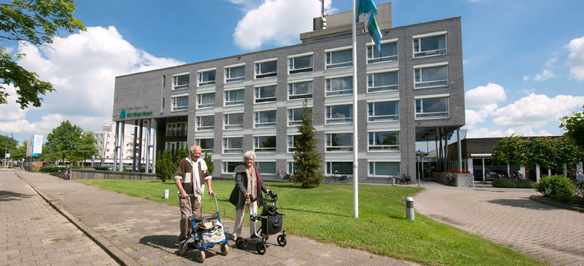 Man en vrouw lopen buiten met rollator op stoep, op achtergrond gebouw Het Hoge Heem in Uithoorn