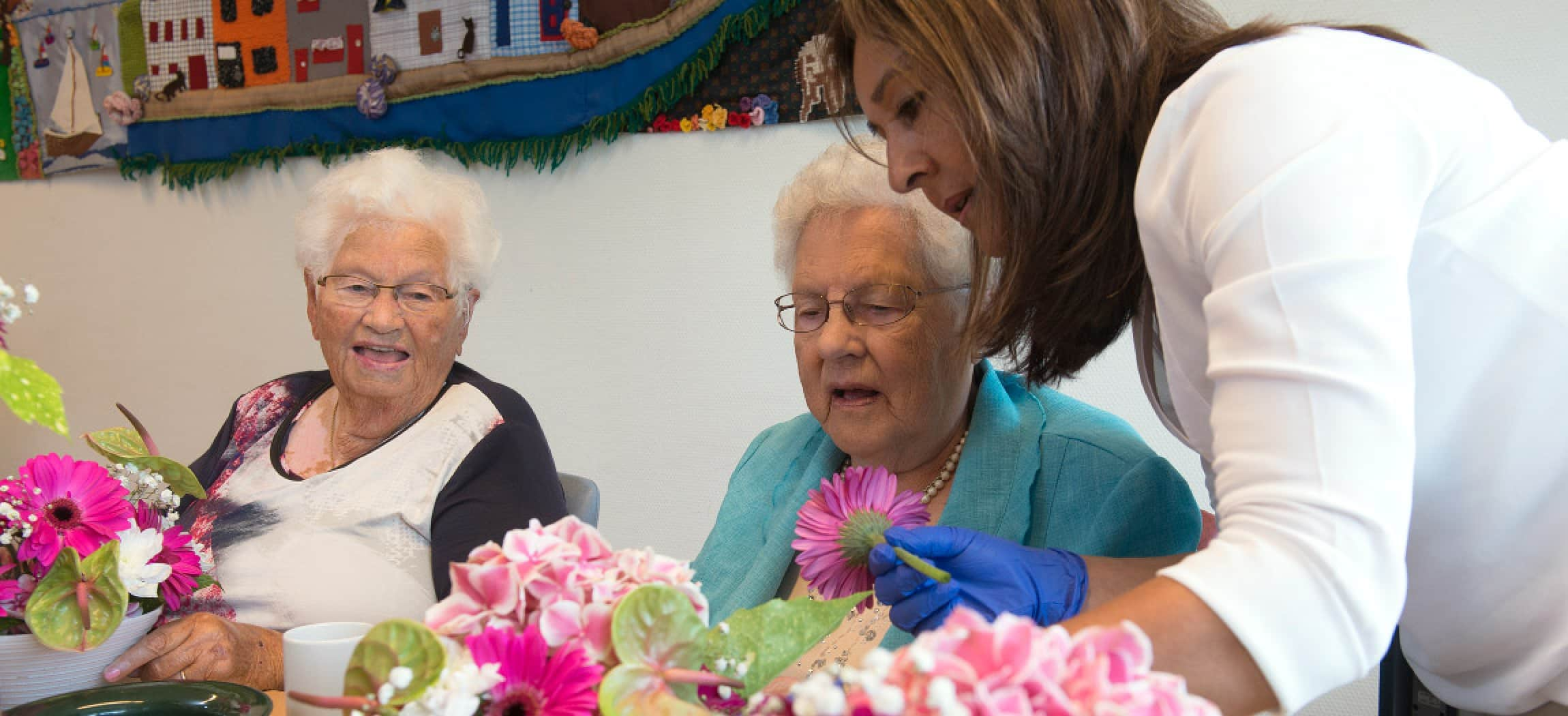 Twee vrouwen kijken naar bloemen op tafel bij bloemschikken